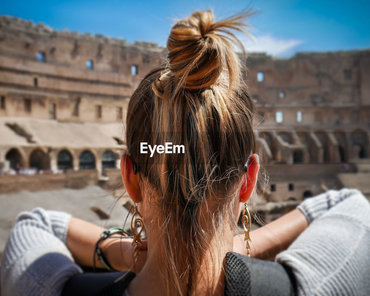 Rear view of woman in front of coliseum