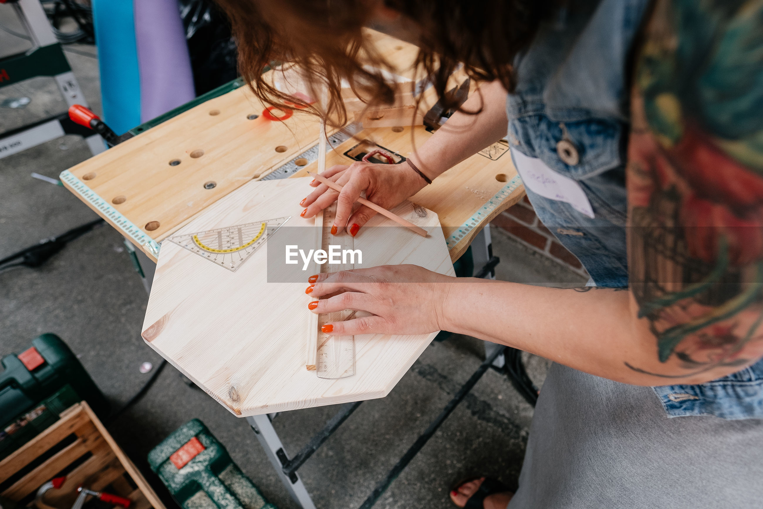 High angle view of woman measuring wood in workshop
