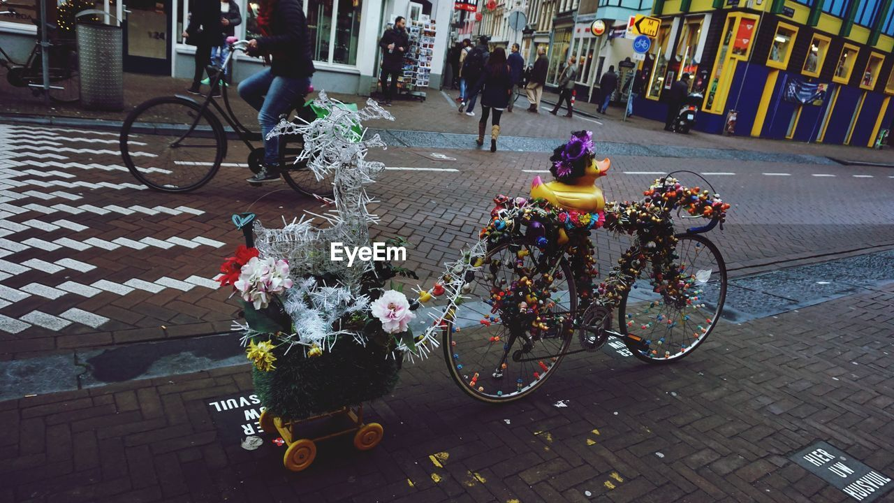 bicycle, flower, land vehicle, transportation, mode of transport, street, real people, outdoors, city life, day, building exterior, bicycle basket, riding, architecture, city, men, medium group of people, women, built structure, sidewalk, stationary, lifestyles, bouquet, bicycle rack, freshness, people