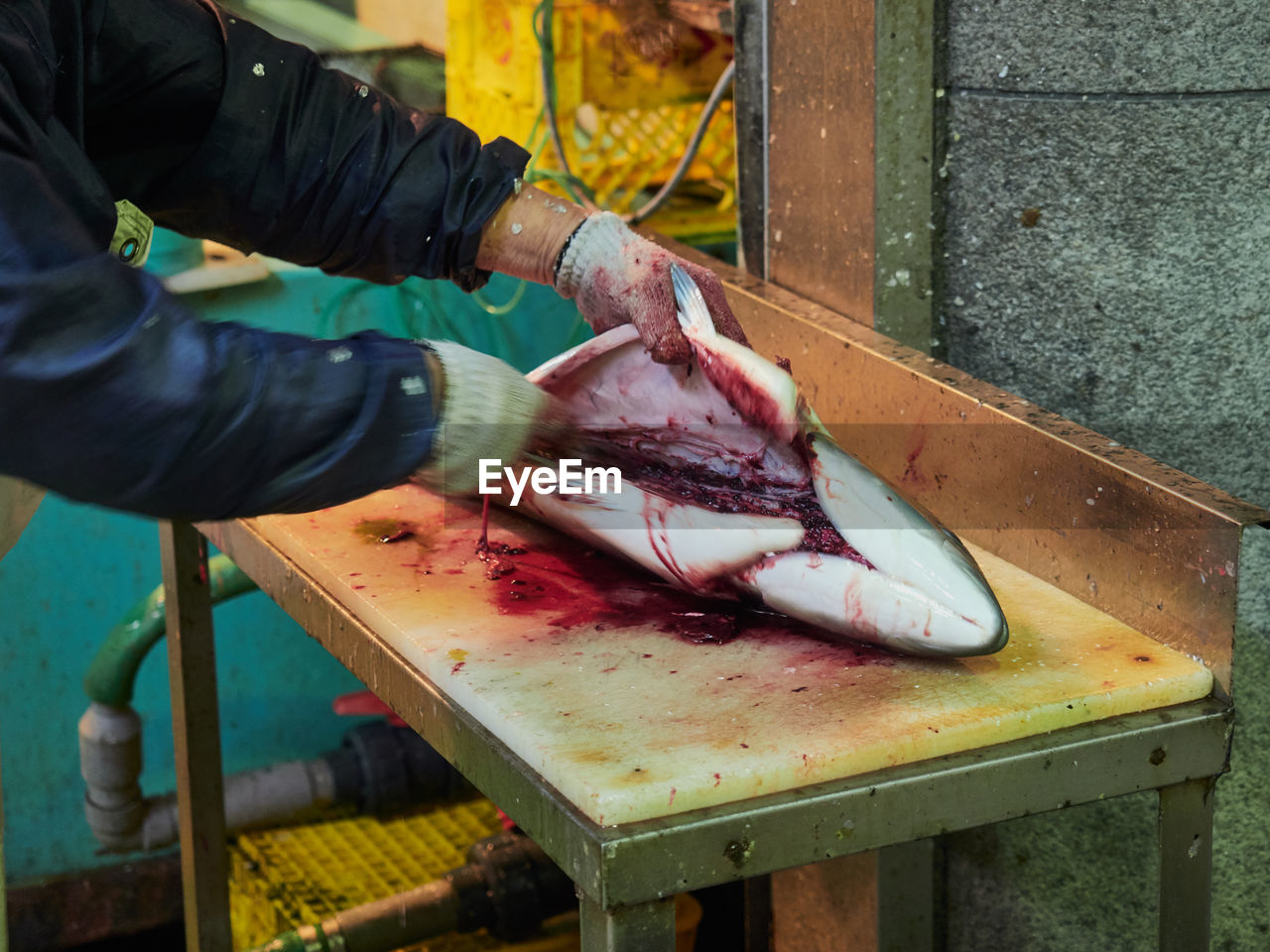 Cropped Hands Of Butcher Cutting Fish At Market