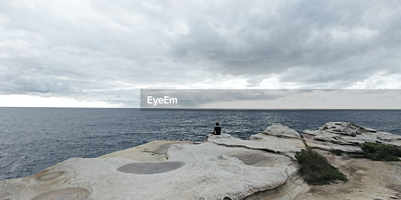Rear view of man looking at sea while sitting on rock formation against cloudy sky