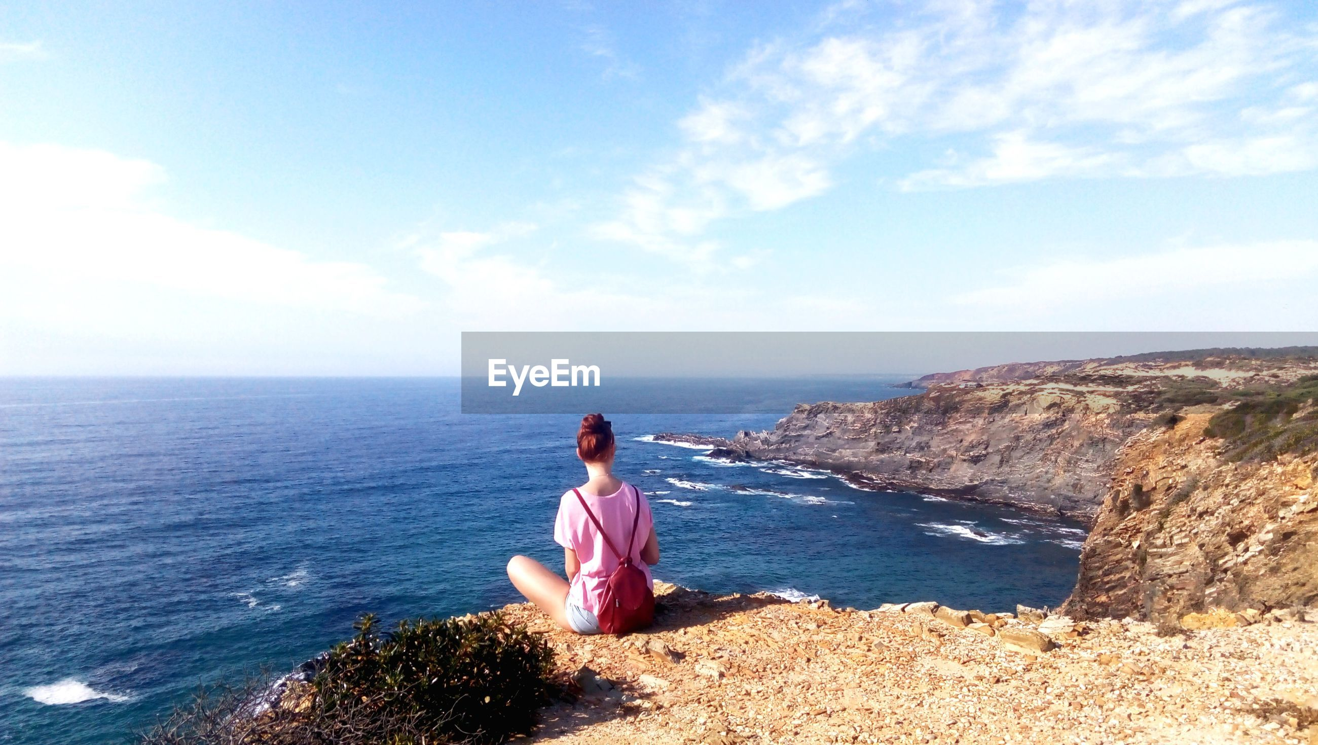Rear view of woman sitting on cliff with sea in background against blue sky