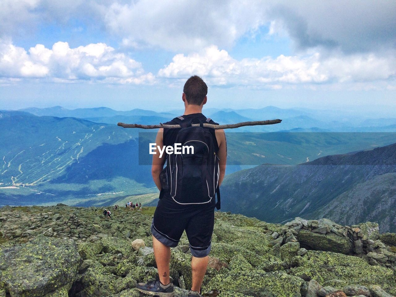 Rear View Of Man With Backpack Standing On Mountain Against Sky