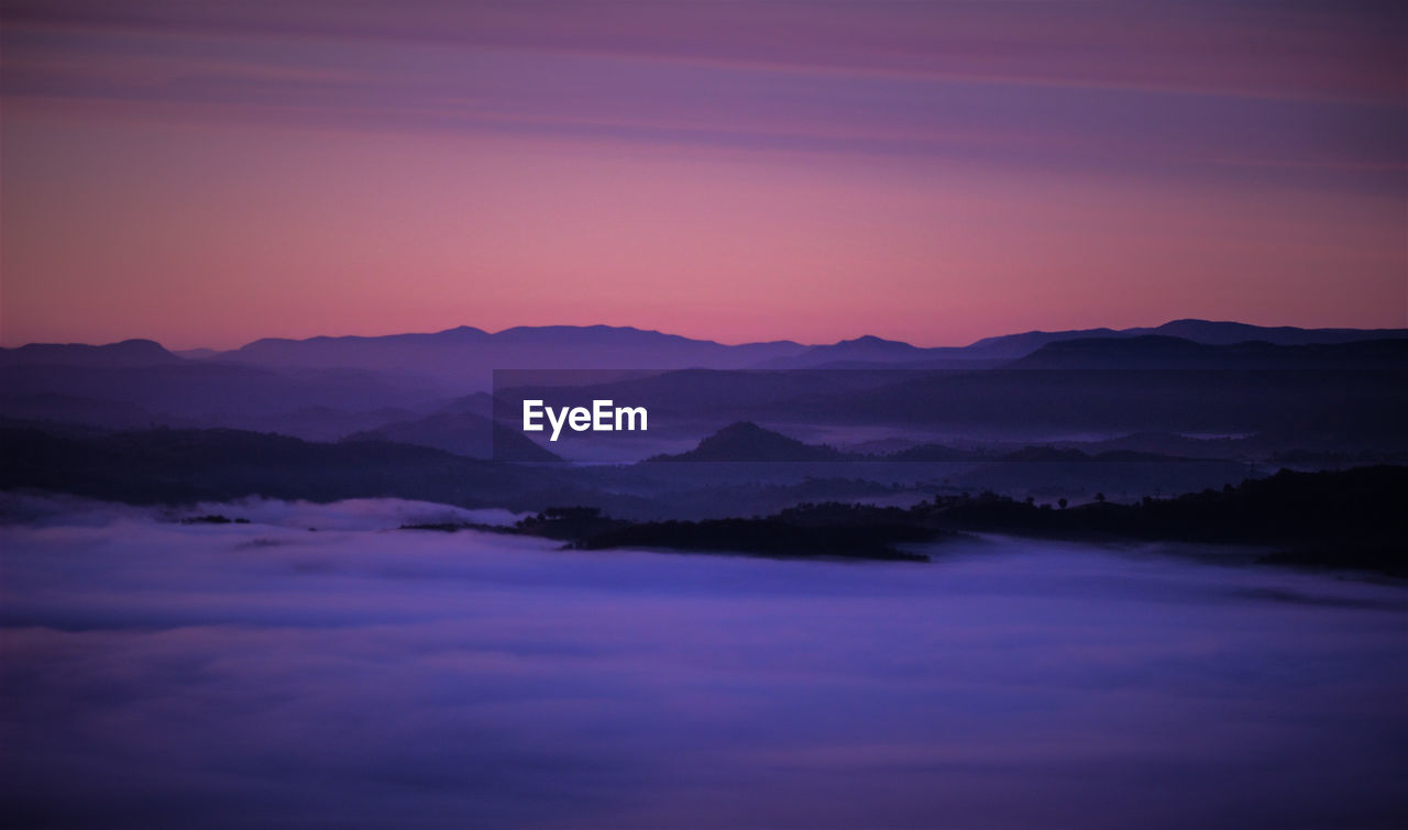 Scenic View Of Silhouette Mountains Against Sky At Sunset