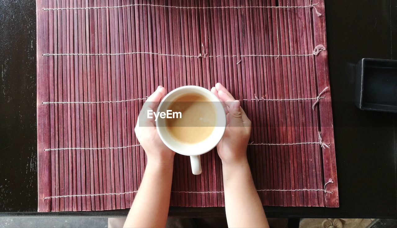 Cropped hands of woman having coffee at table