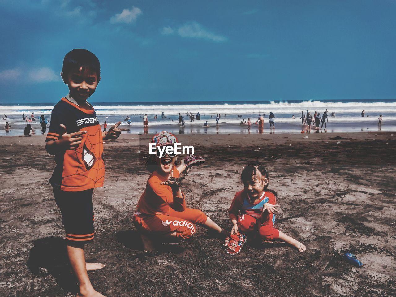 CHILDREN ON BEACH AGAINST SKY