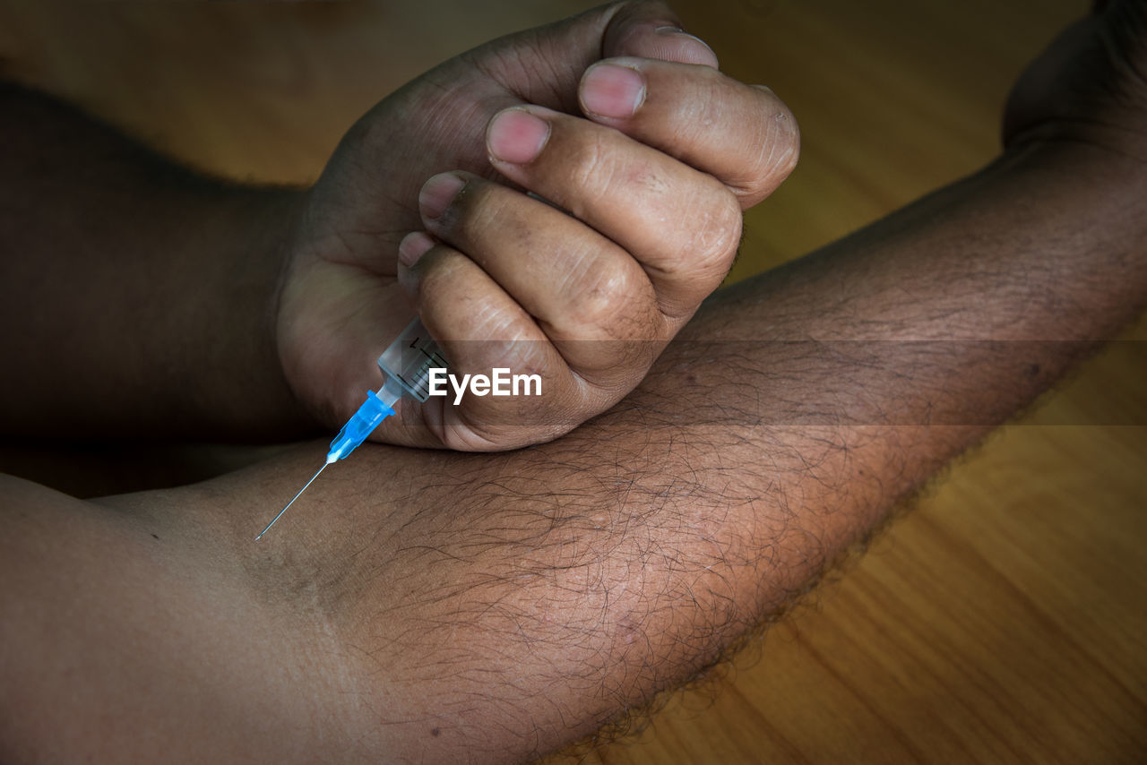 Cropped Image Of Man Injecting Arm