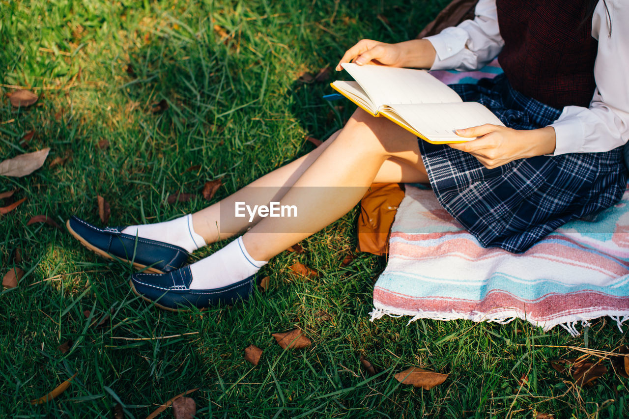 Low section of woman reading book while sitting in park