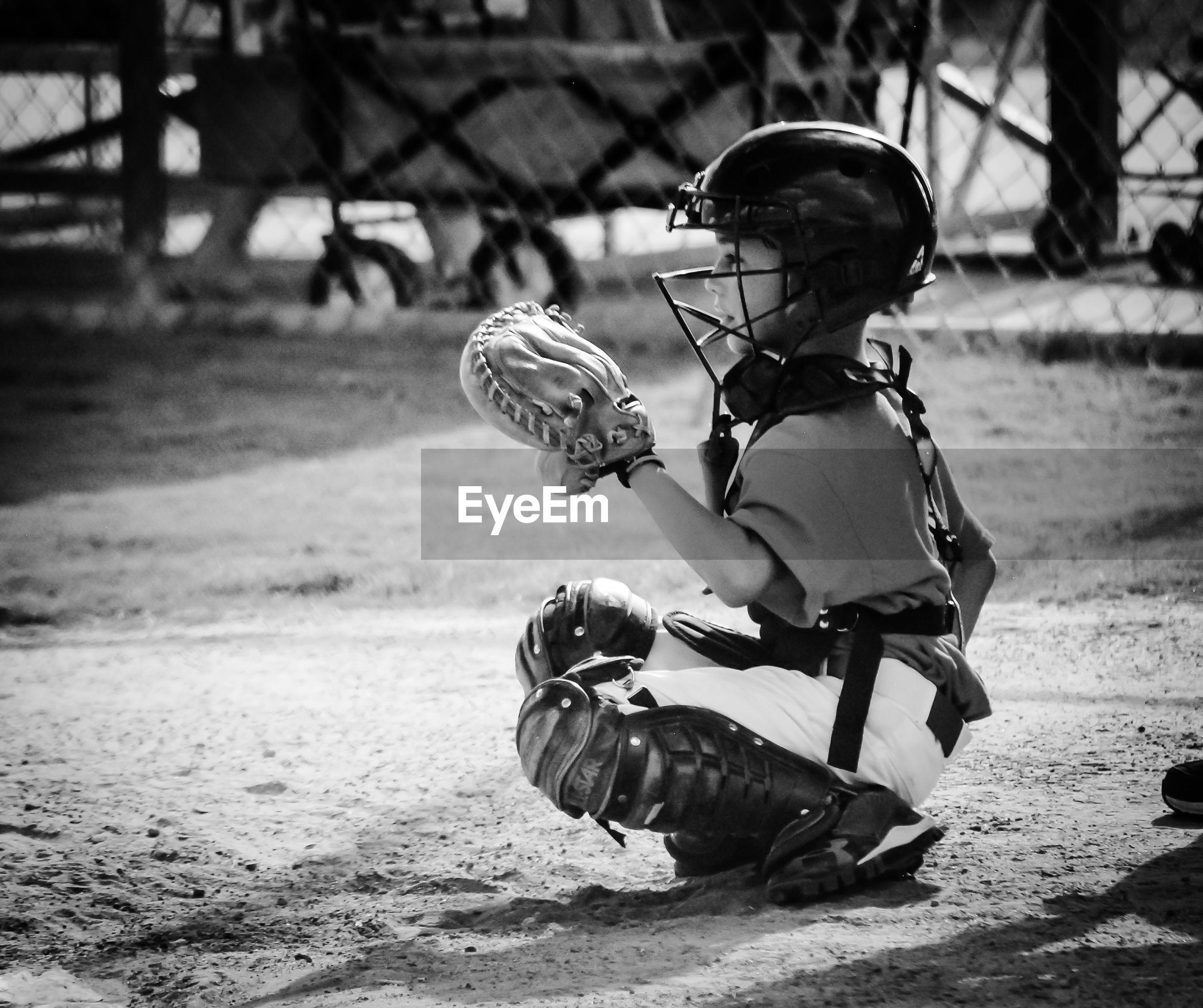 Full length of baseball catcher on field