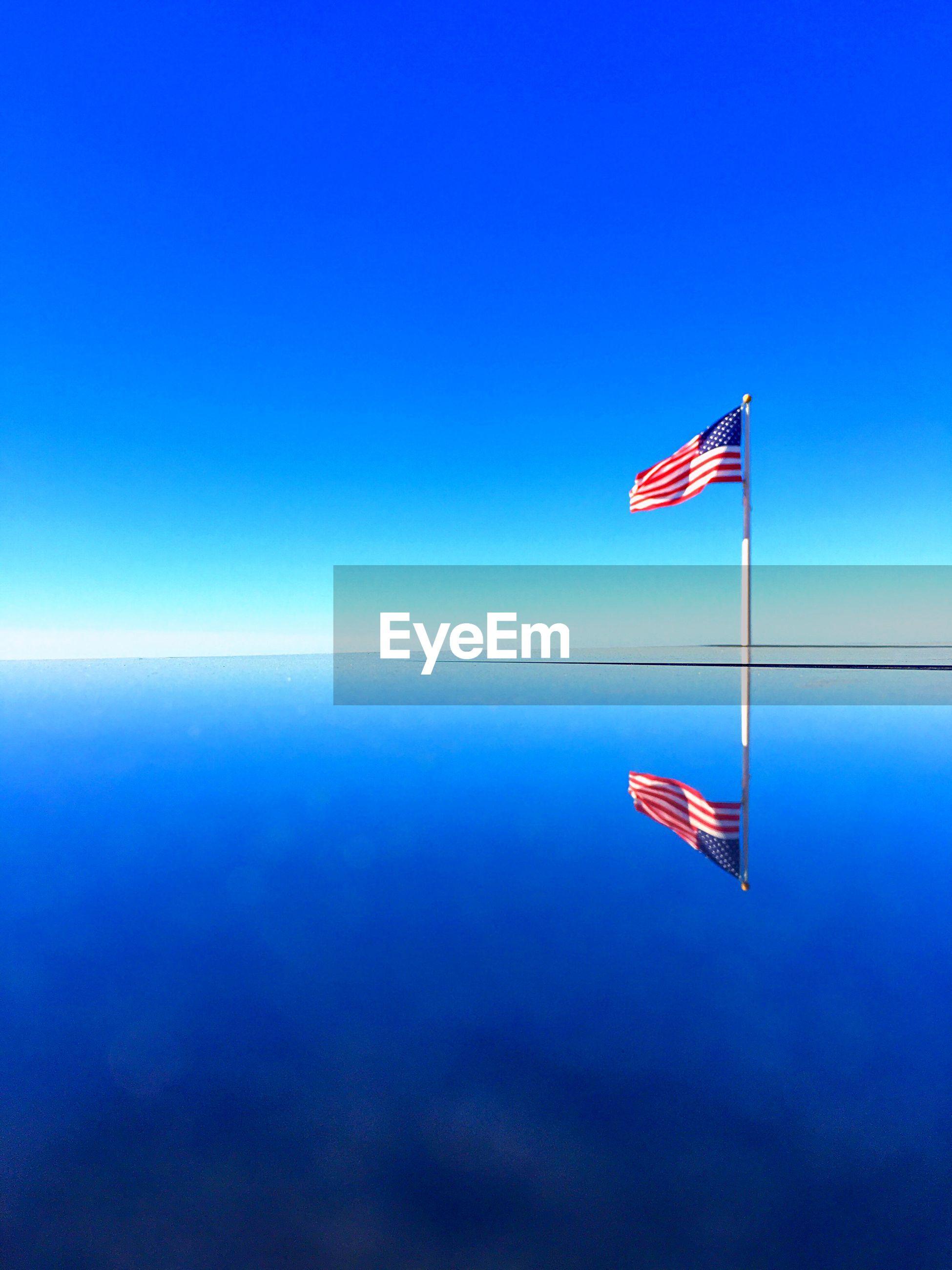 American flag in sea against clear blue sky