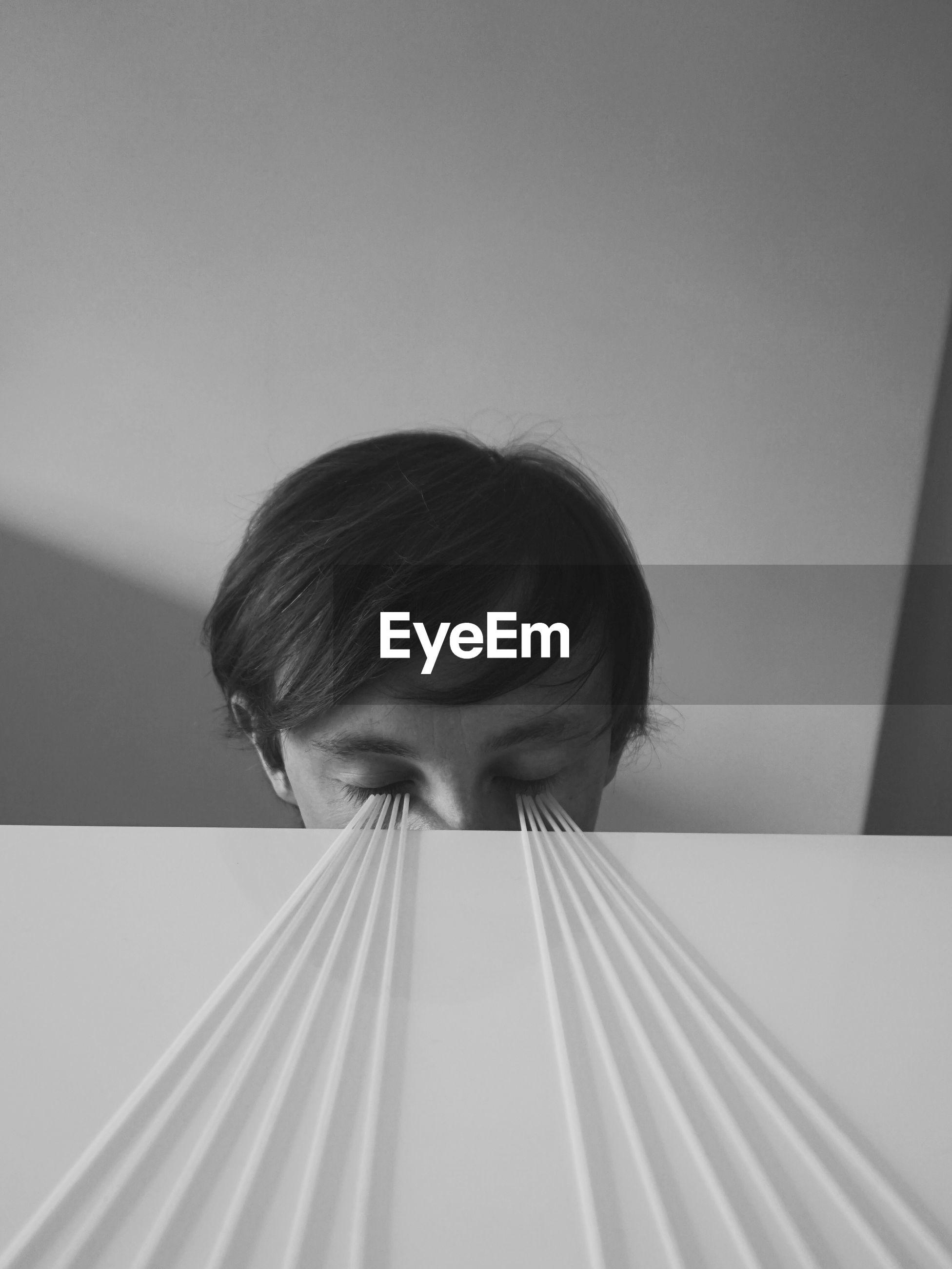 Spaghetti on table leading towards man closed eyes