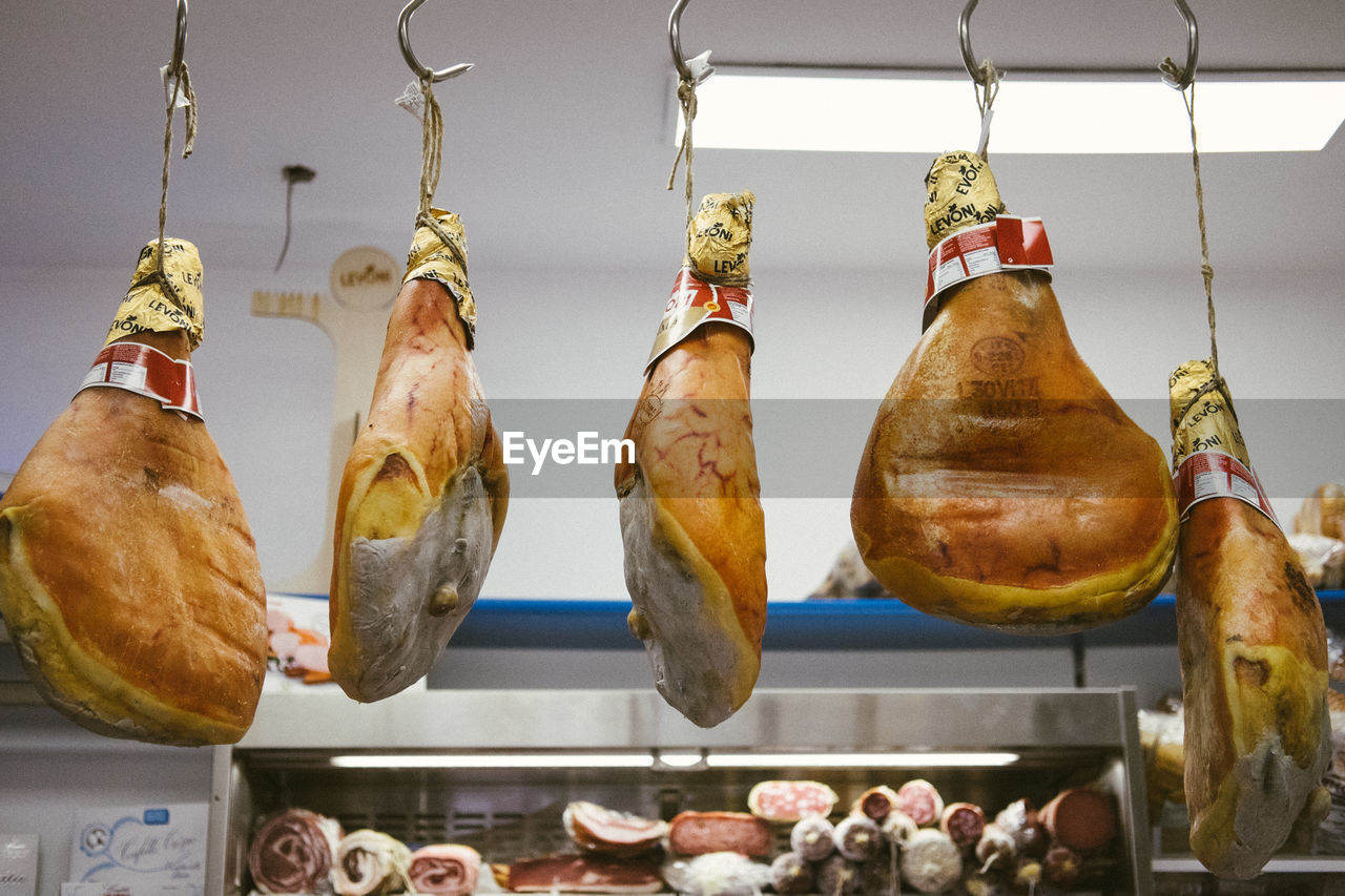 food and drink, hanging, meat, food, freshness, for sale, retail, processed meat, side by side, raw food, ham, pork, still life, indoors, in a row, no people, hook, choice, market, retail display, sale