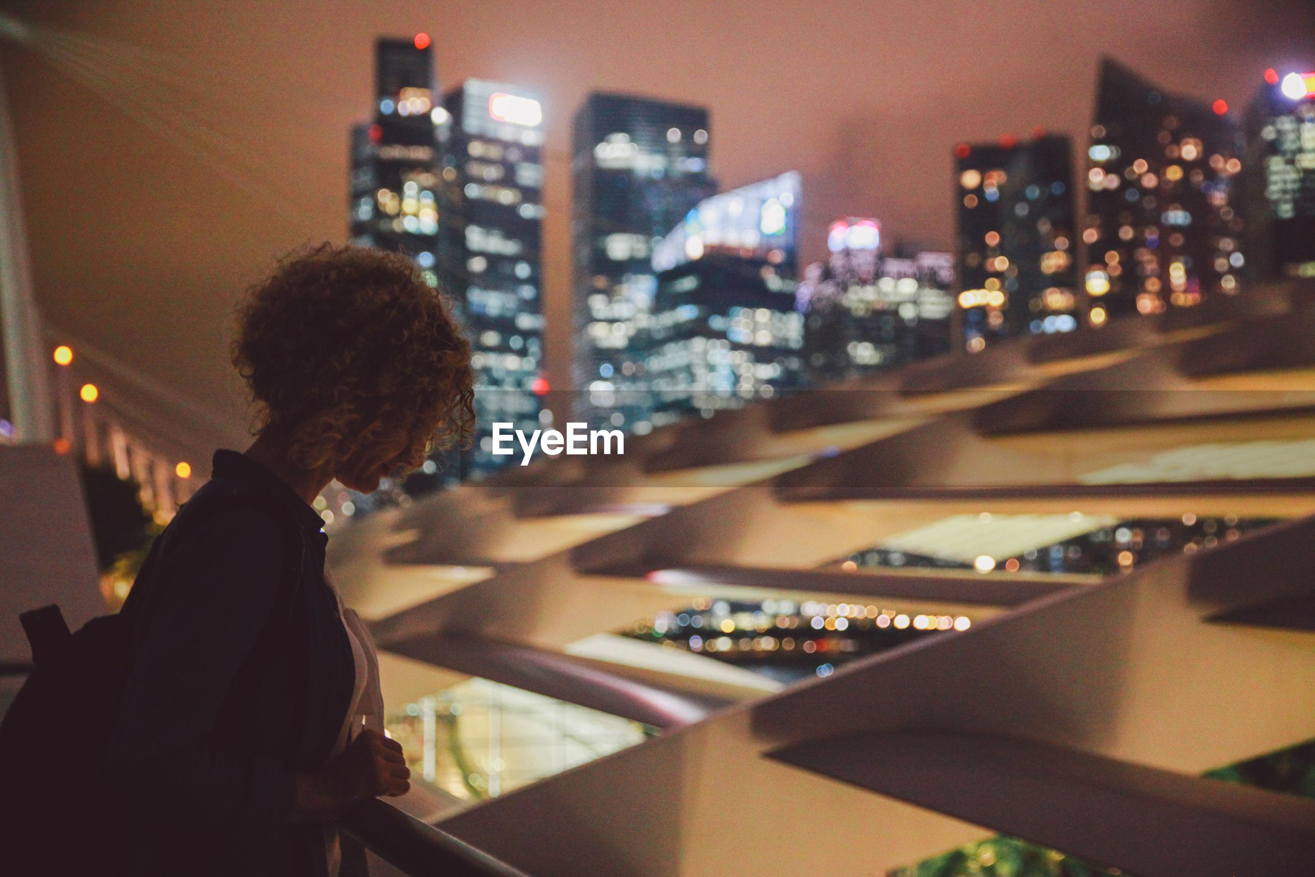 Woman standing at railing against illuminated city at night