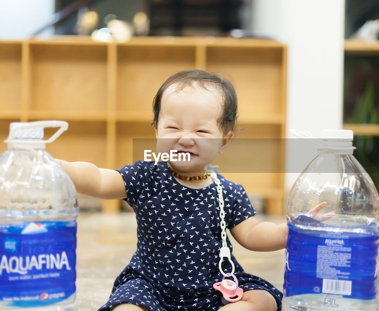 bottle, real people, one person, childhood, innocence, casual clothing, front view, lifestyles, water bottle, food and drink, focus on foreground, smiling, milk bottle, happiness, cute, drink, day, indoors, food, freshness
