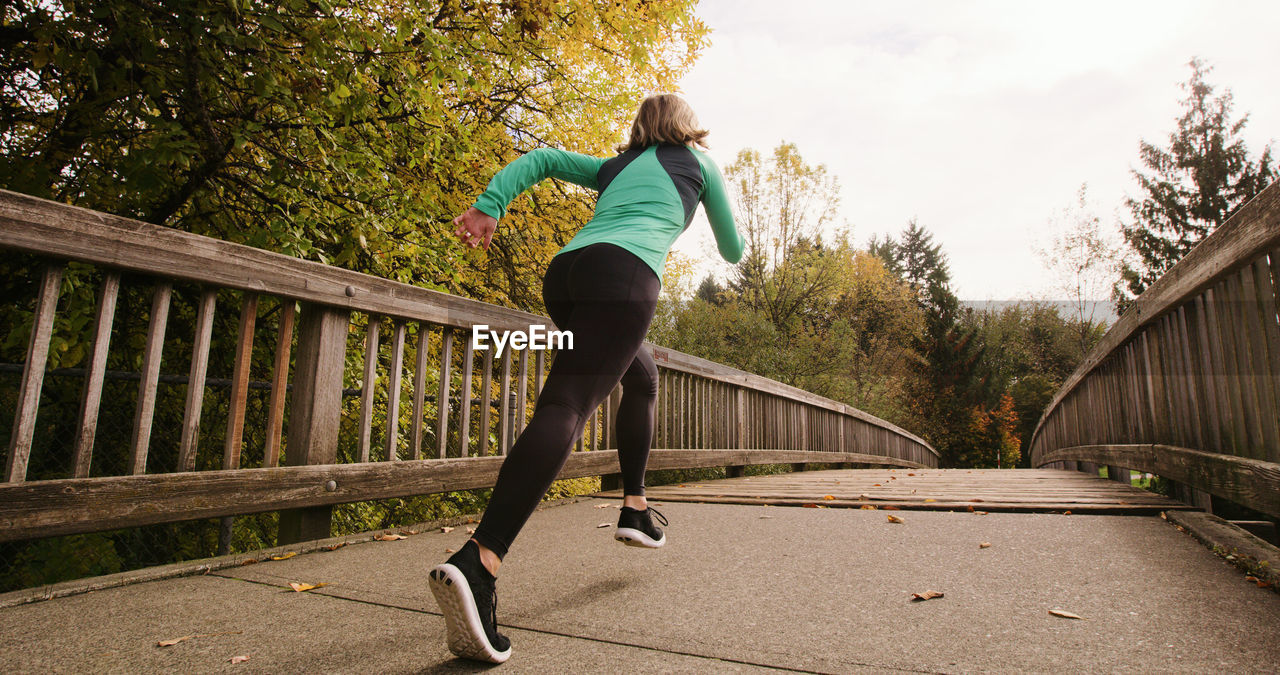Young Woman On Running On Footbridge Against Sky