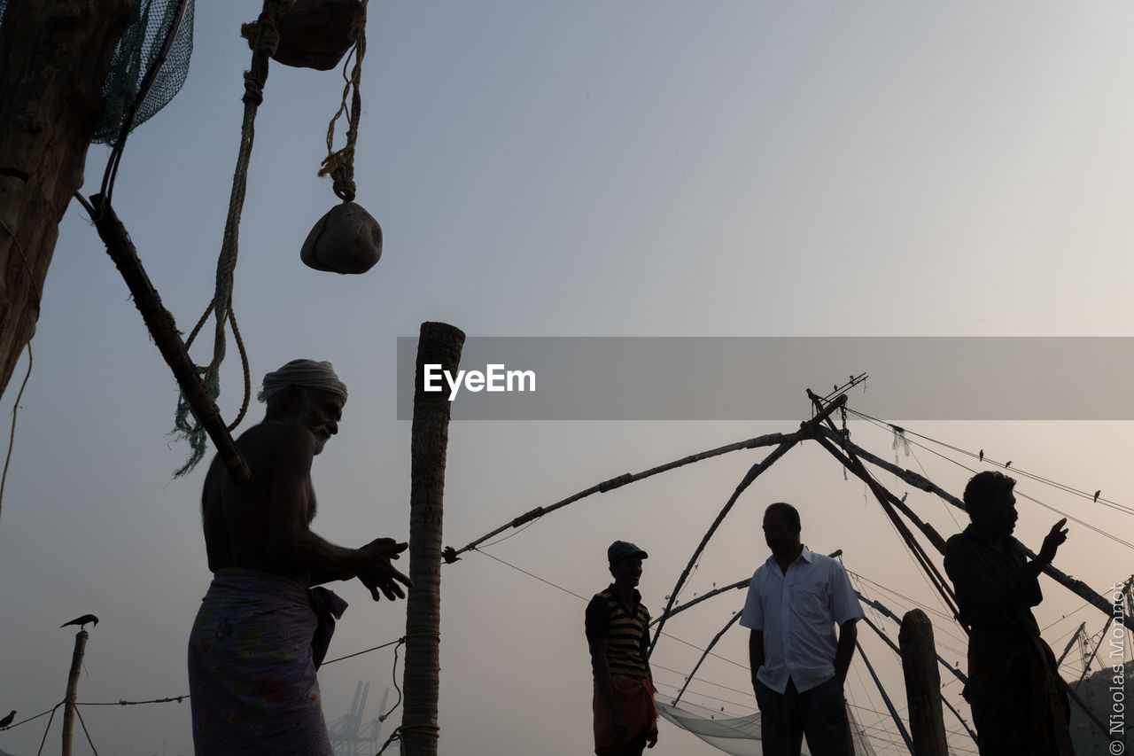 real people, fishing net, men, fisherman, fishing, casual clothing, sky, outdoors, clear sky, nautical vessel, lifestyles, low angle view, standing, nature, women, togetherness, working, teamwork, day, people