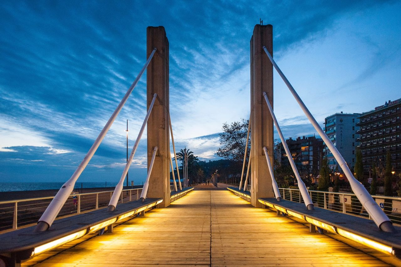 bridge - man made structure, connection, the way forward, architecture, built structure, suspension bridge, sky, outdoors, cloud - sky, transportation, day, travel destinations, no people, low angle view, footbridge, water, city