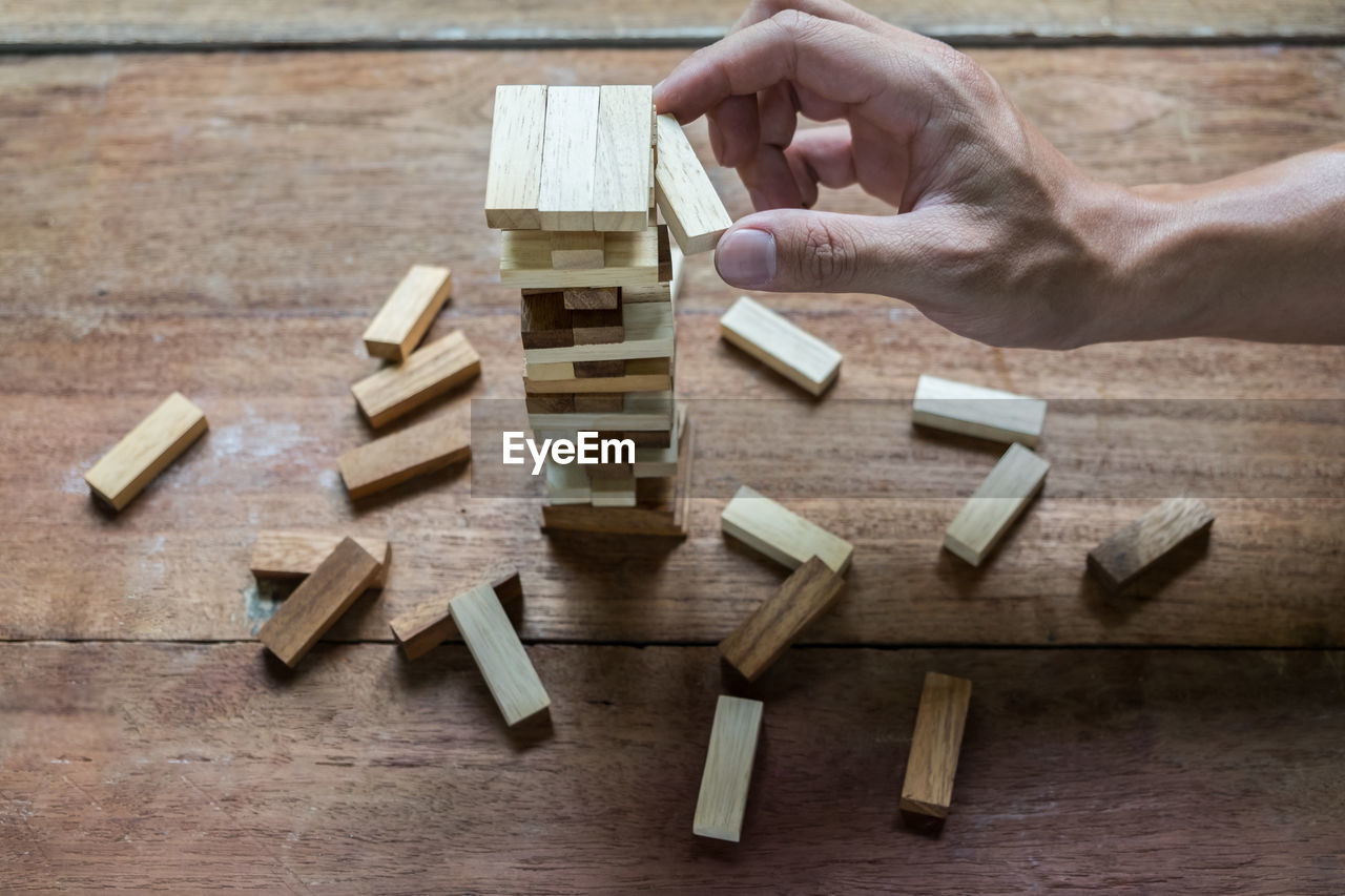 Cropped Image Of Hand Playing With Toy Blocks On Table
