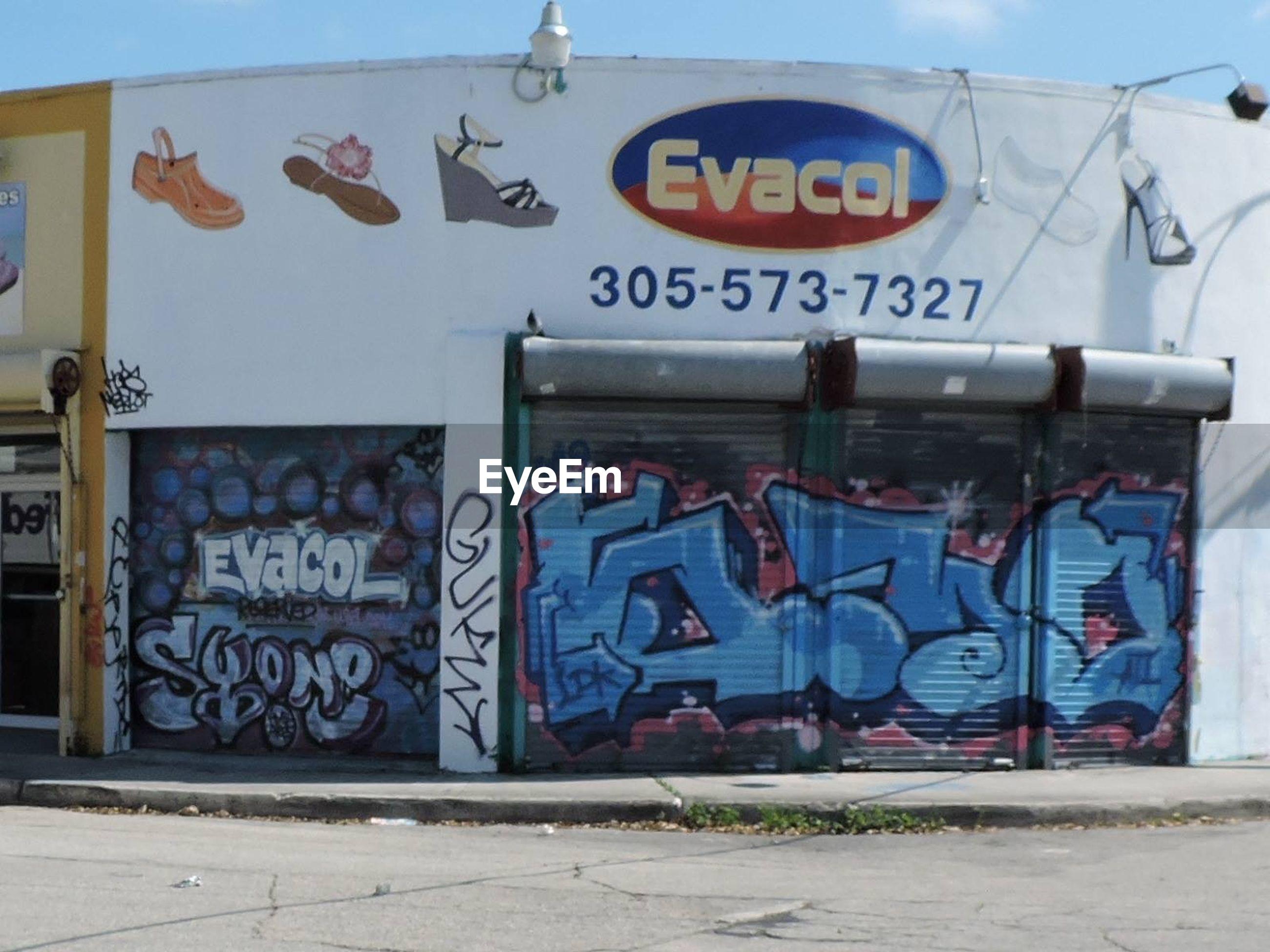 graffiti, text, architecture, built structure, western script, art, wall - building feature, building exterior, creativity, communication, art and craft, street art, day, wall, no people, outdoors, blue, human representation, sunlight, non-western script