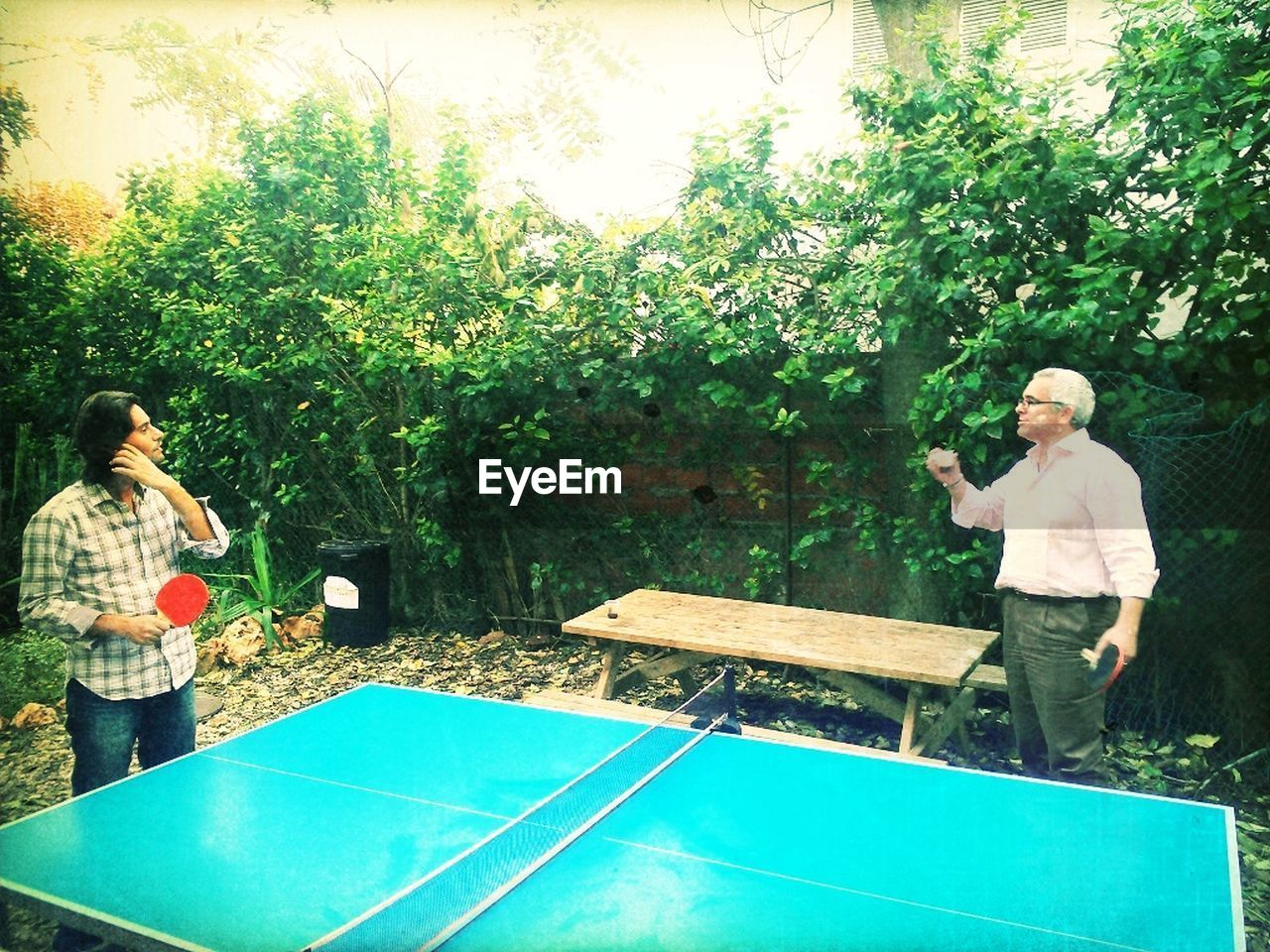 table tennis, standing, two people, casual clothing, togetherness, leisure activity, day, mature adult, tree, outdoors, mature men, holding, enjoyment, men, lifestyles, young adult, sport, playing, adult, real people, full length, young women, people, adults only, nature