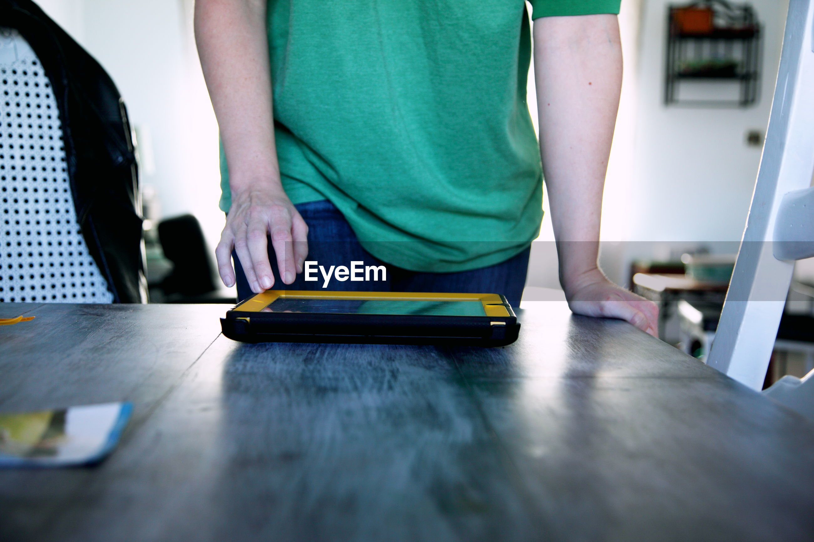 Midsection of man using digital tablet on table