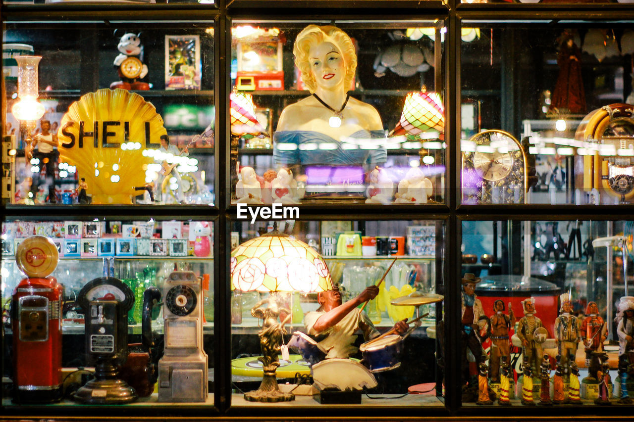 choice, retail, variation, store, human representation, illuminated, representation, shopping, indoors, adult, food and drink, arts culture and entertainment, retail display, female likeness, group of people, male likeness, portrait, shelf, waist up, people
