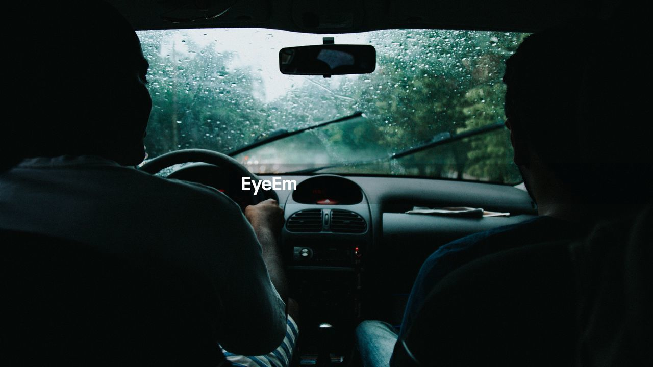 Man with friend driving car during rainy season