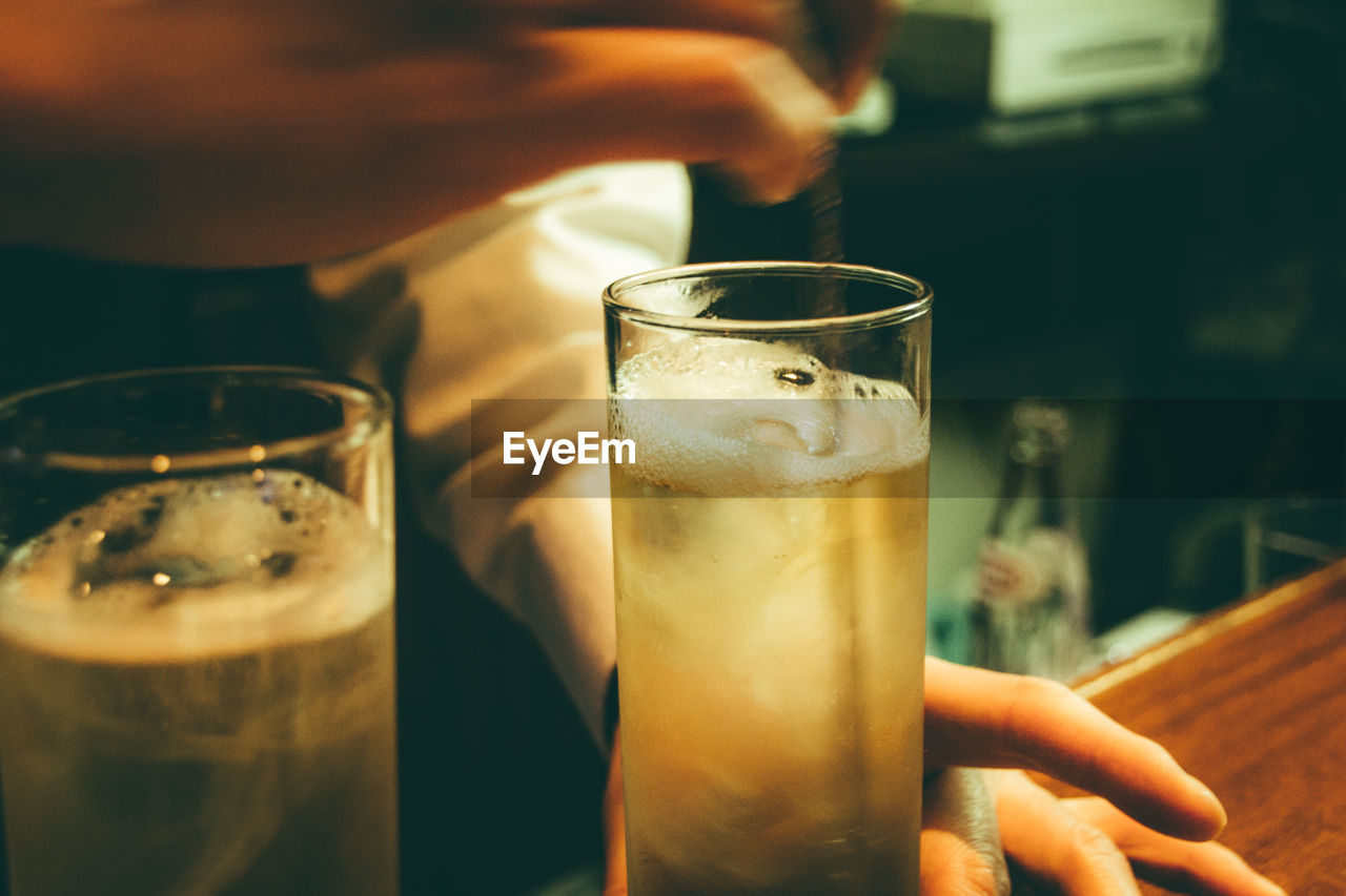 Cropped hands of bartender stirring alcohol in glass on bar counter