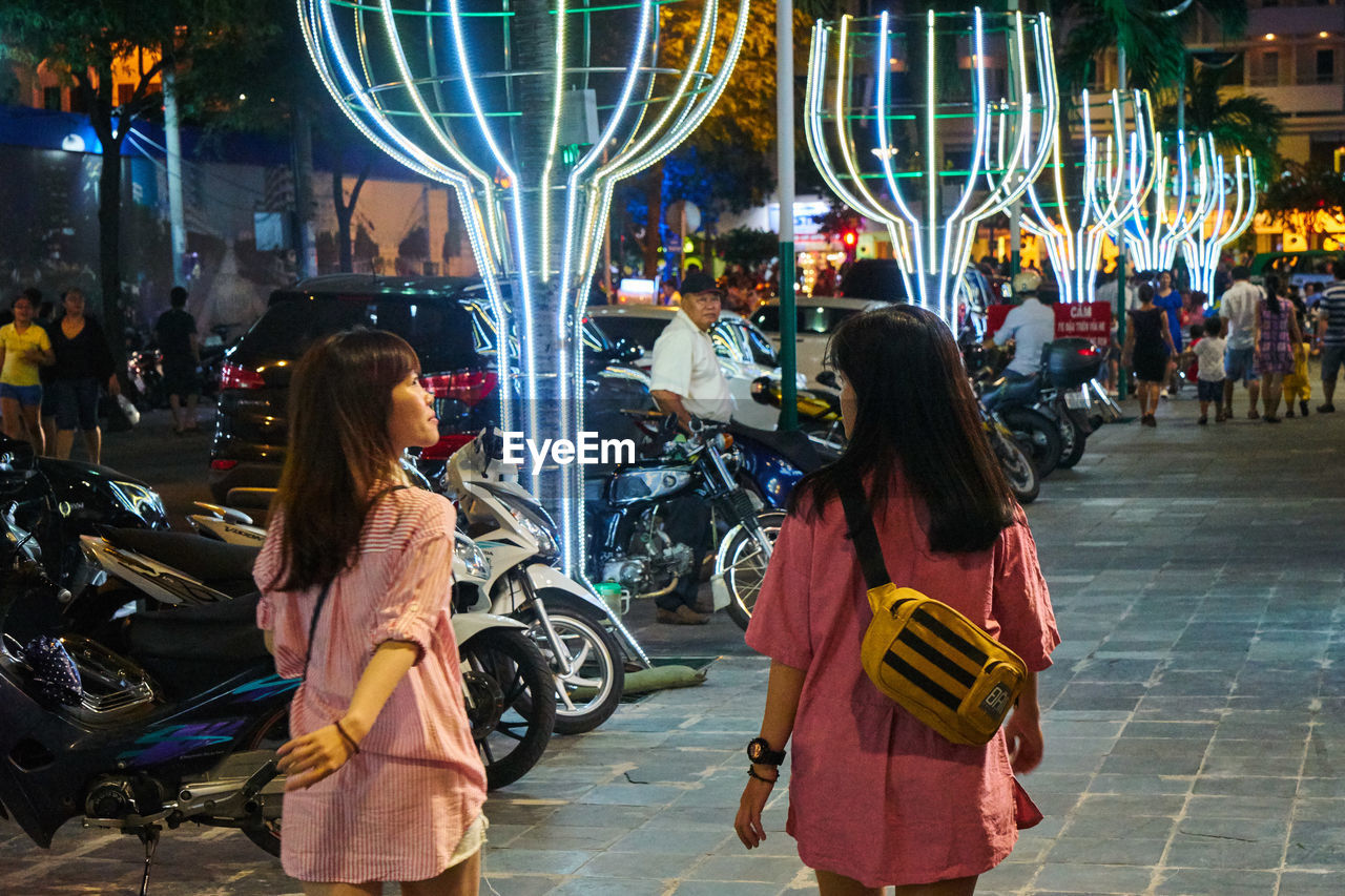 night, retail, rear view, consumerism, real people, store, two people, illuminated, city life, customer, buying, lifestyles, women, standing, leisure activity, city, sitting, young adult, young women, outdoors, adult, people, adults only