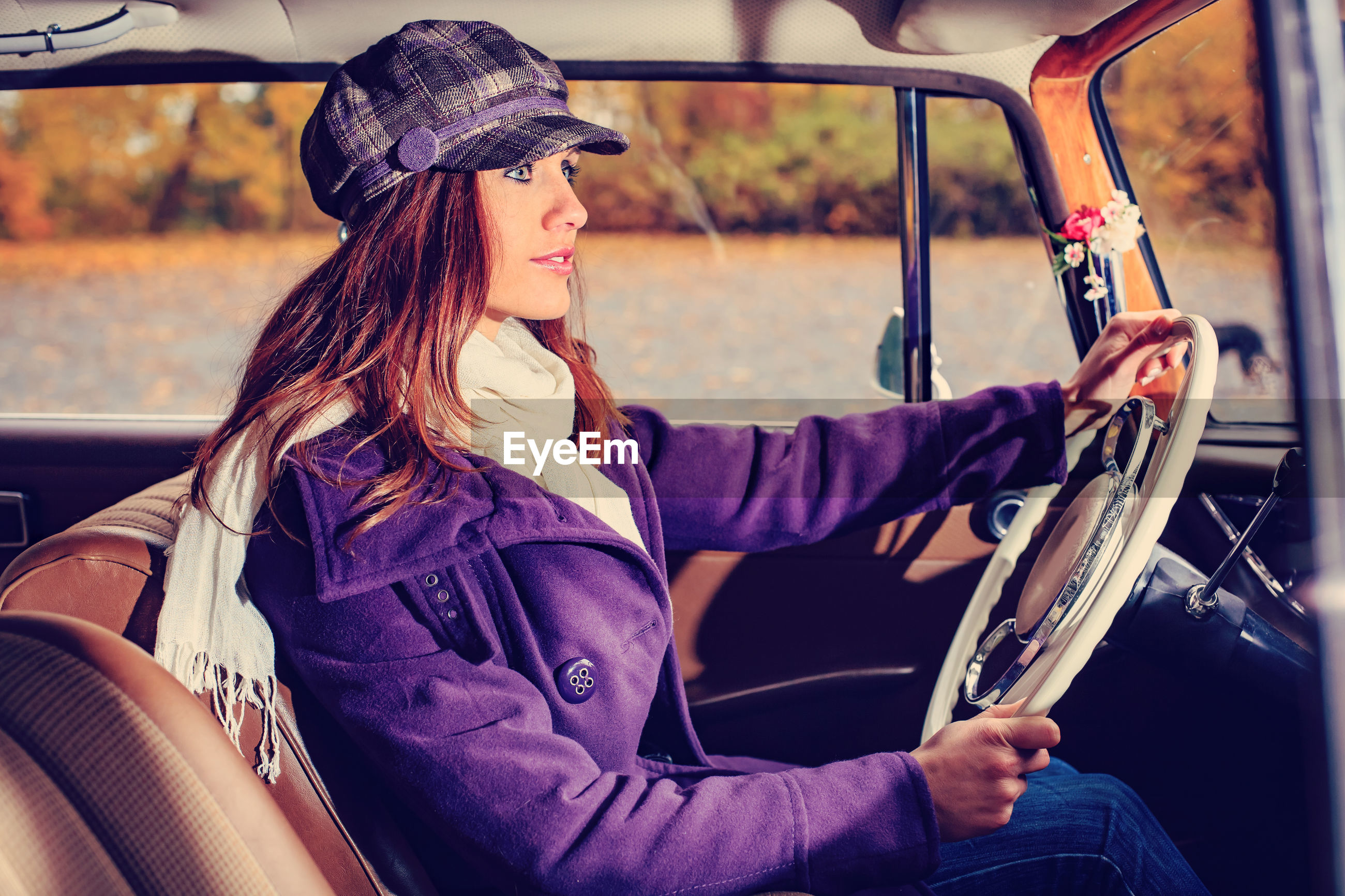 Side view of woman wearing warm clothing driving car