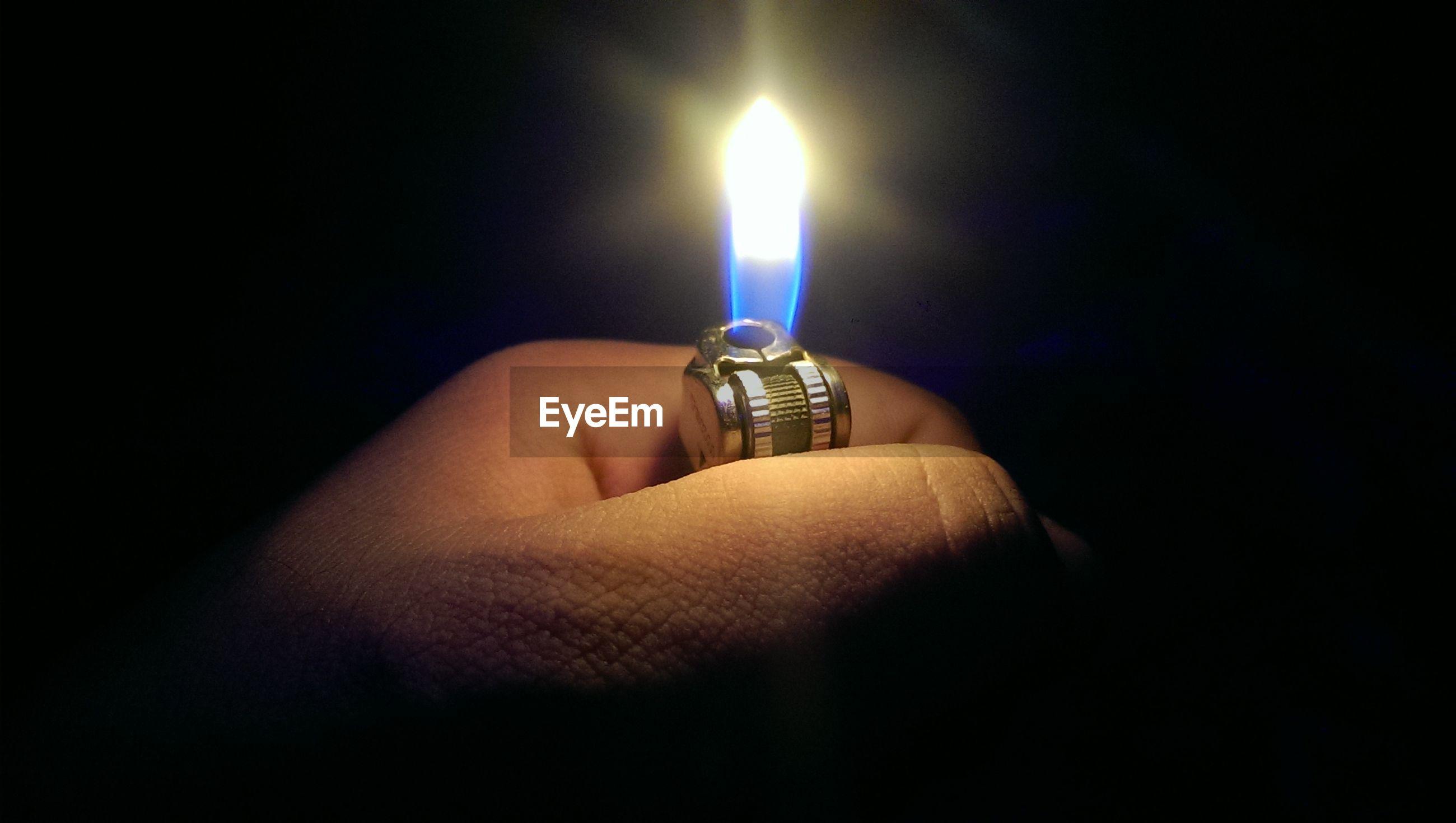 indoors, person, burning, candle, black background, studio shot, flame, illuminated, lit, heat - temperature, glowing, close-up, fire - natural phenomenon, darkroom, part of, dark, lighting equipment