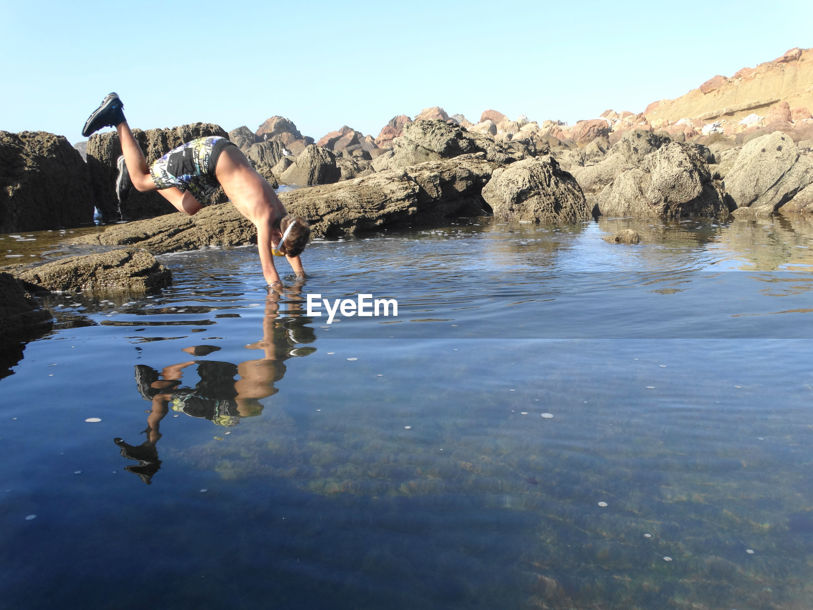 Shirtless boy diving in lake