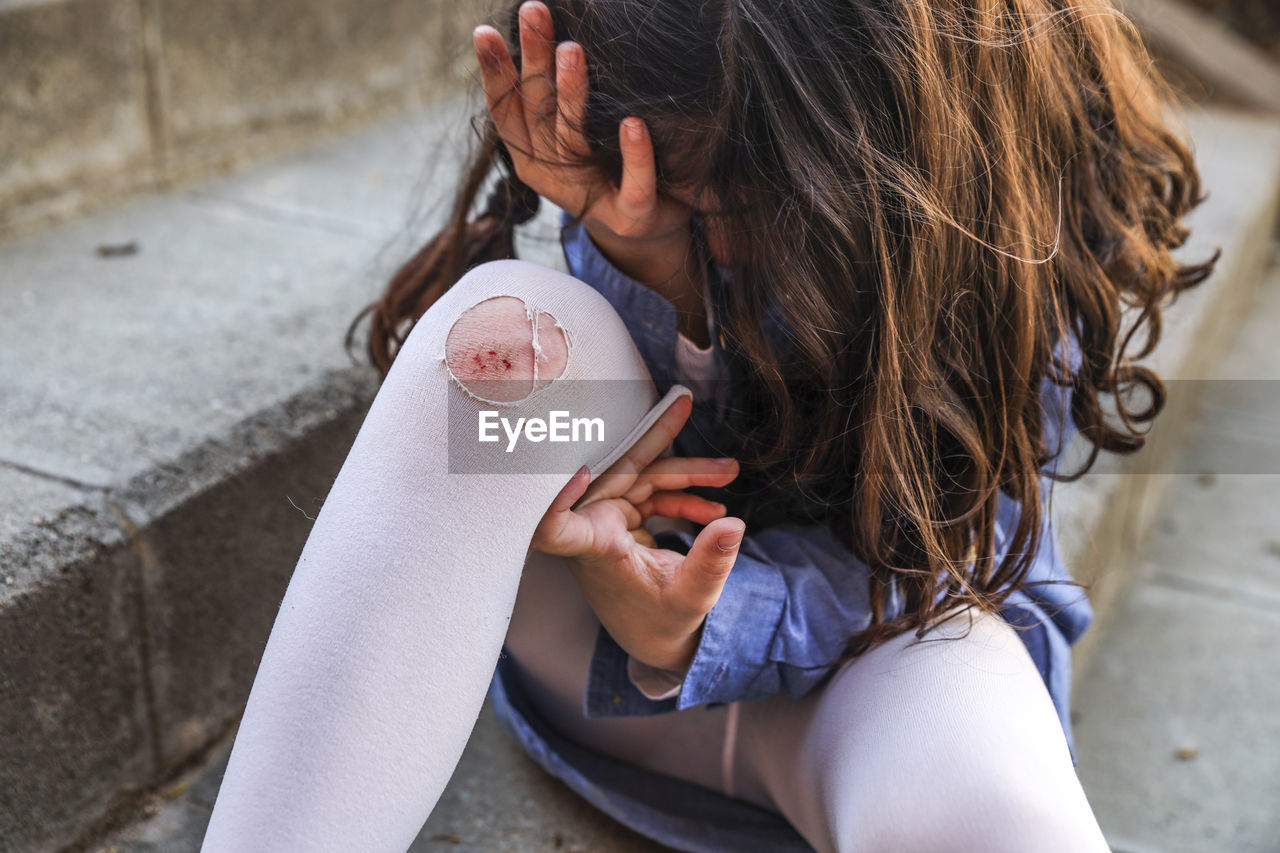 child, childhood, real people, women, girls, lifestyles, day, holding, females, focus on foreground, food and drink, one person, high angle view, leisure activity, casual clothing, food, drink, dairy product, brown hair, innocence, drinking, hairstyle, outdoors