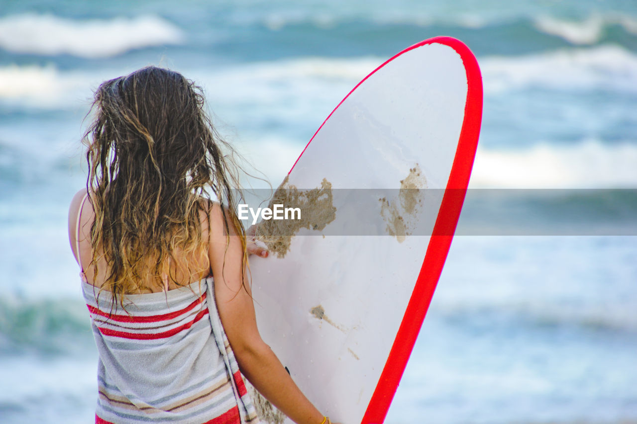 Rear View Of Woman Standing With Surfboard By Sea