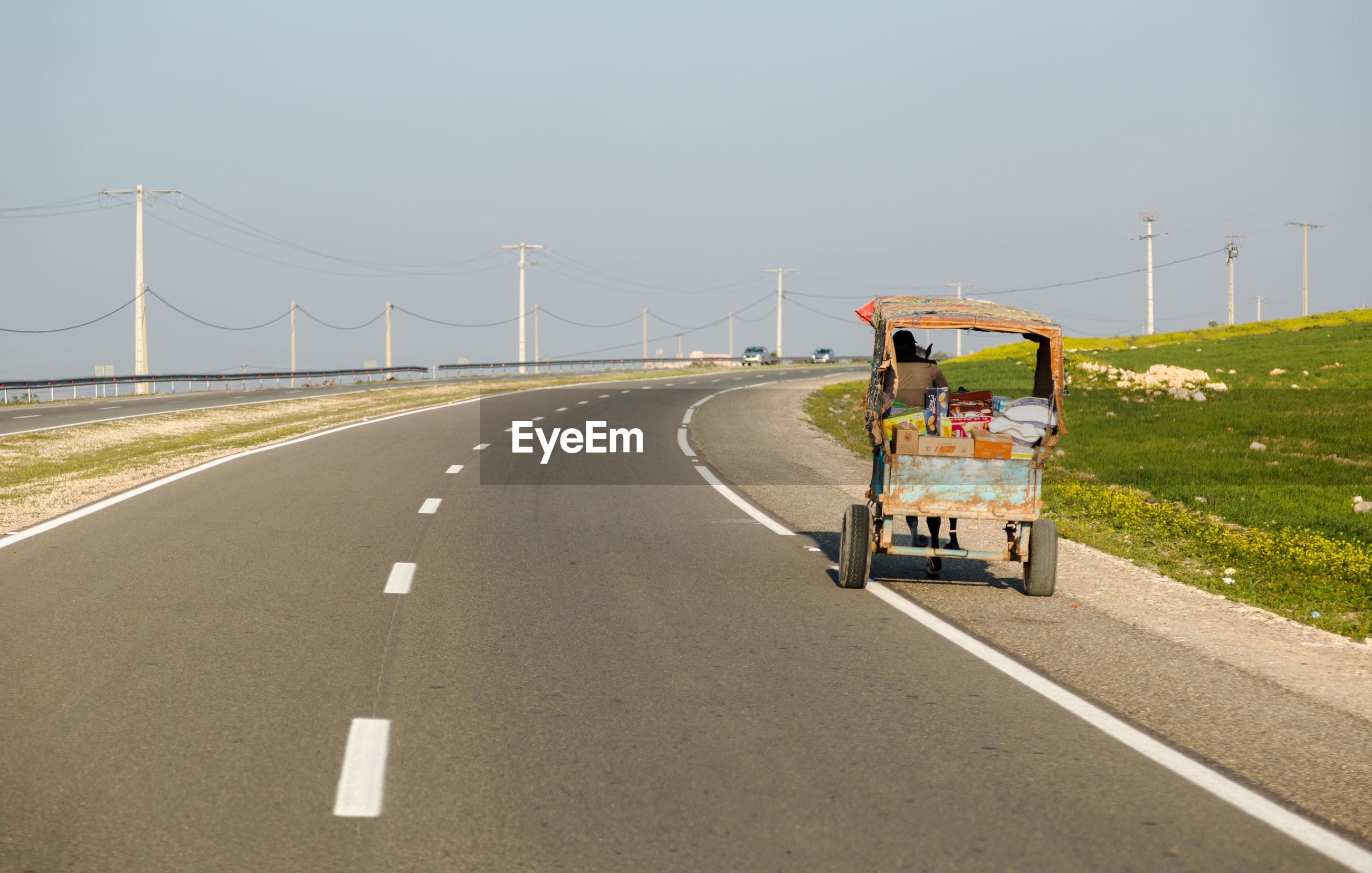 PEOPLE RIDING MOTORCYCLE ON ROAD BY BRIDGE AGAINST SKY