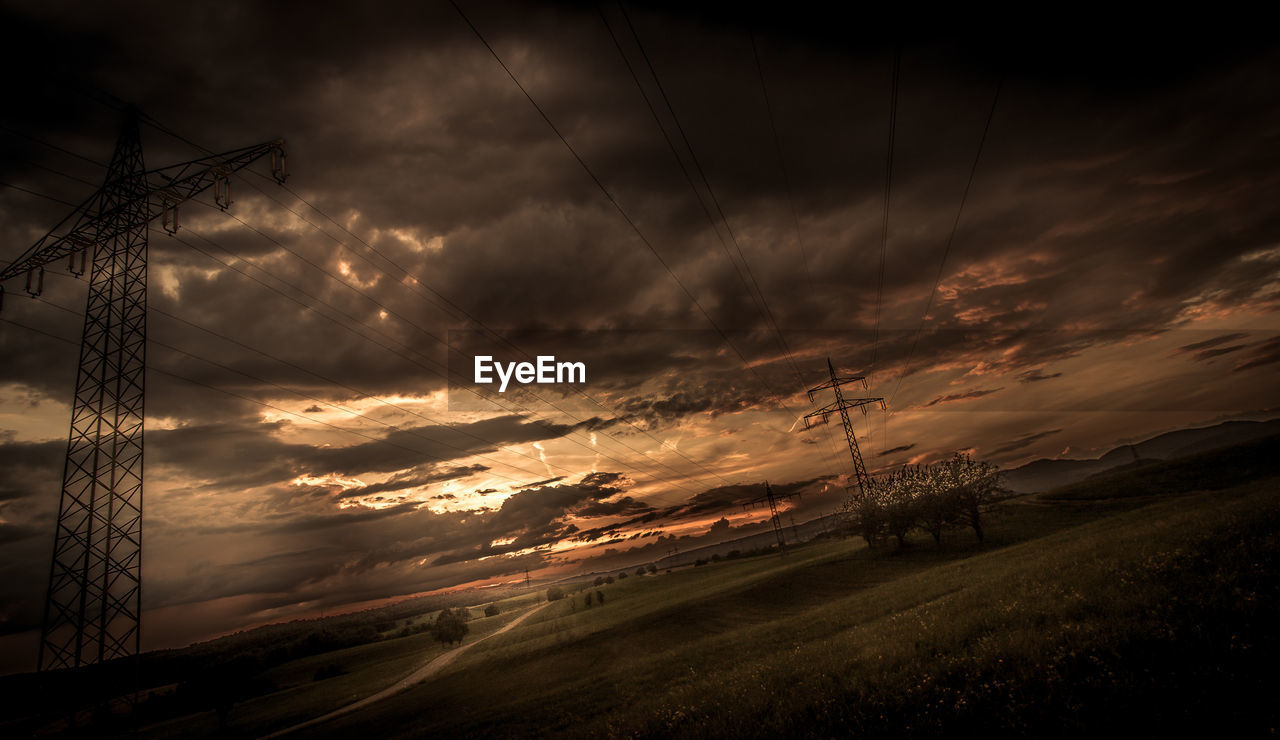 cloud - sky, sky, sunset, electricity, fuel and power generation, electricity pylon, cable, beauty in nature, technology, power line, no people, nature, power supply, connection, orange color, scenics - nature, field, environment, tranquil scene, outdoors