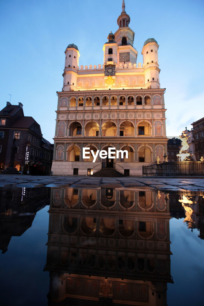 Reflection Of Illuminated Poznan Town Hall In Puddle Against Sky At Twilight
