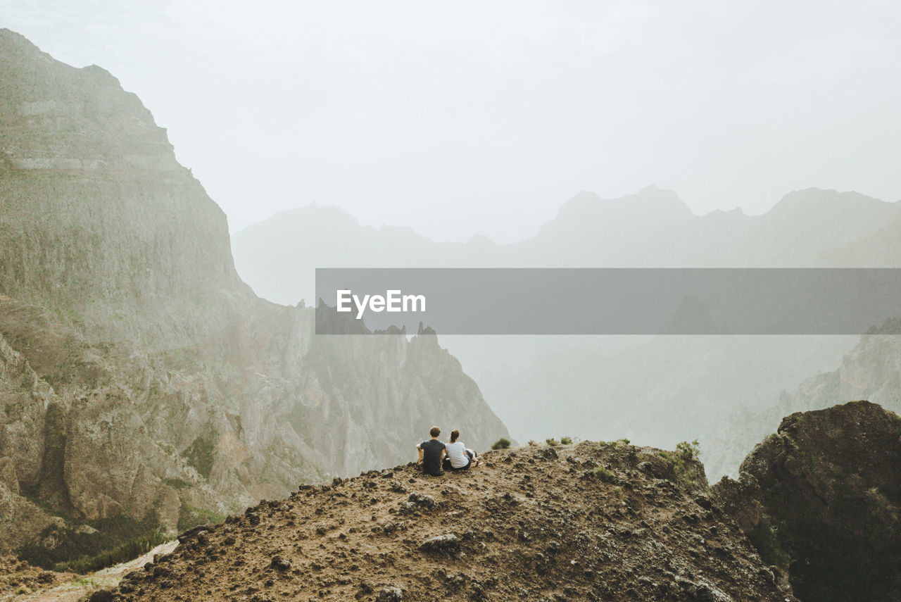 Rear View Of People Sitting On Cliff By Mountains Against Sky