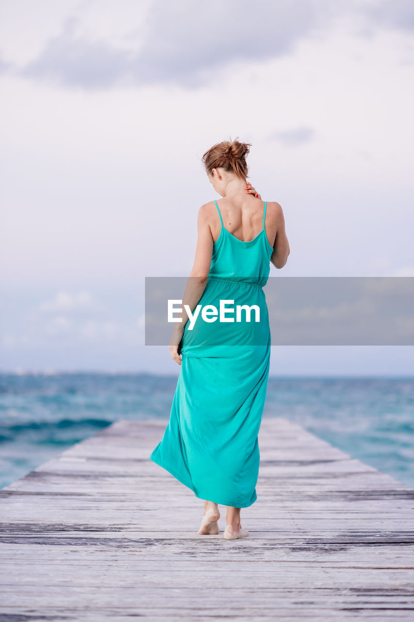 Rear View Of Woman Walking On Pier Against Sea