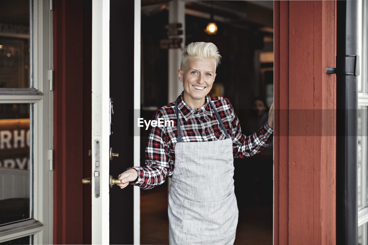 looking at camera, standing, smiling, one person, portrait, adult, happiness, front view, emotion, lifestyles, senior adult, door, entrance, real people, casual clothing, holding, waist up, confidence, white hair