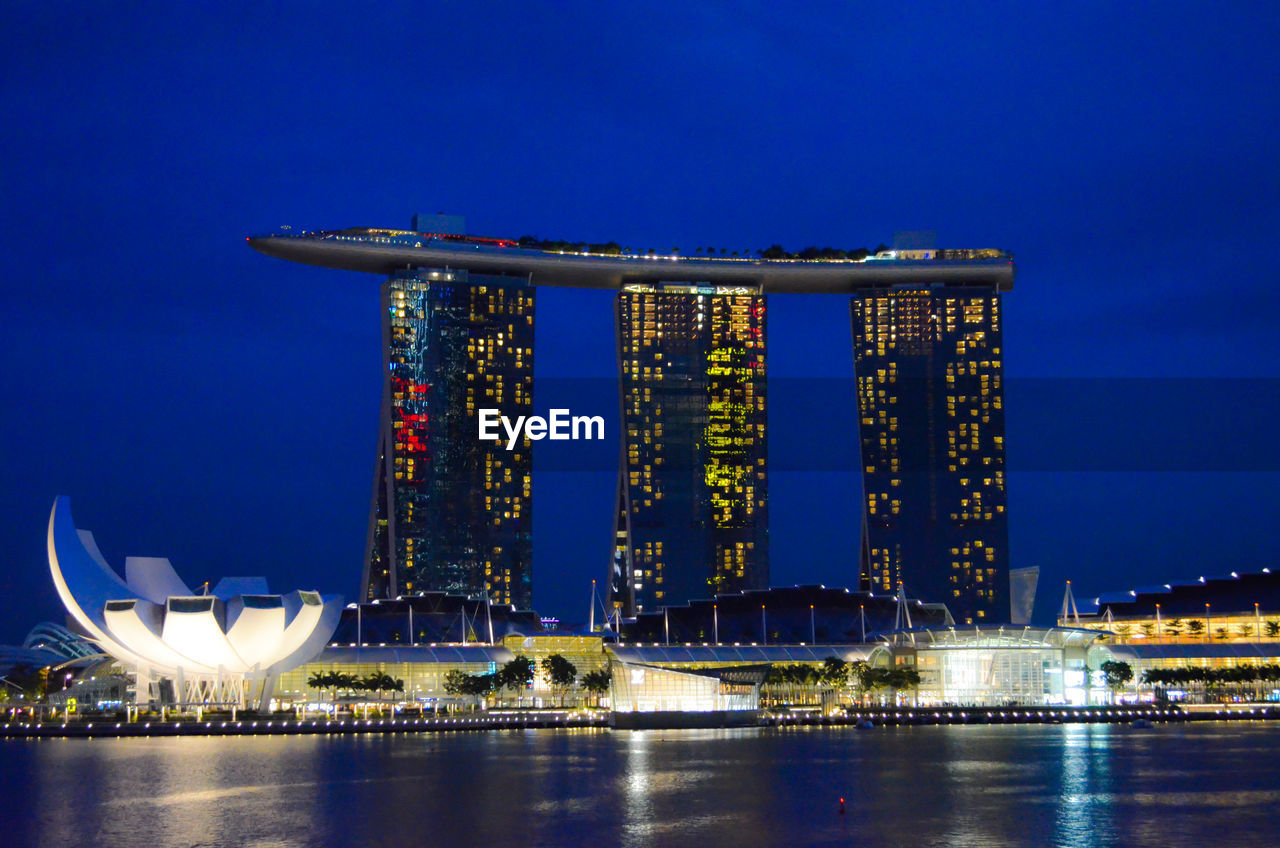 Illuminated Marina Bay Sands In City By River Against Blue Sky At Night