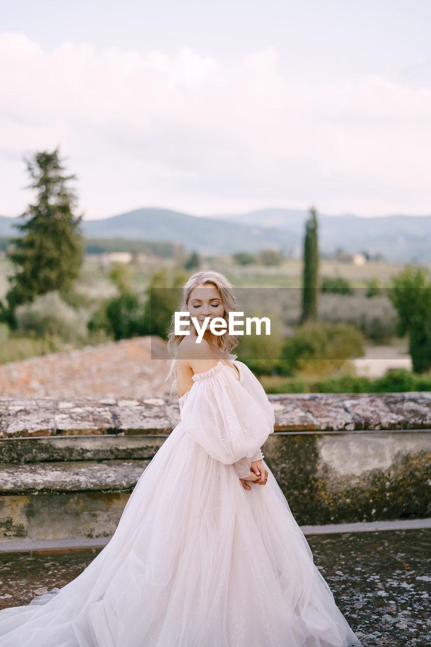 Smiling bride standing against landscape
