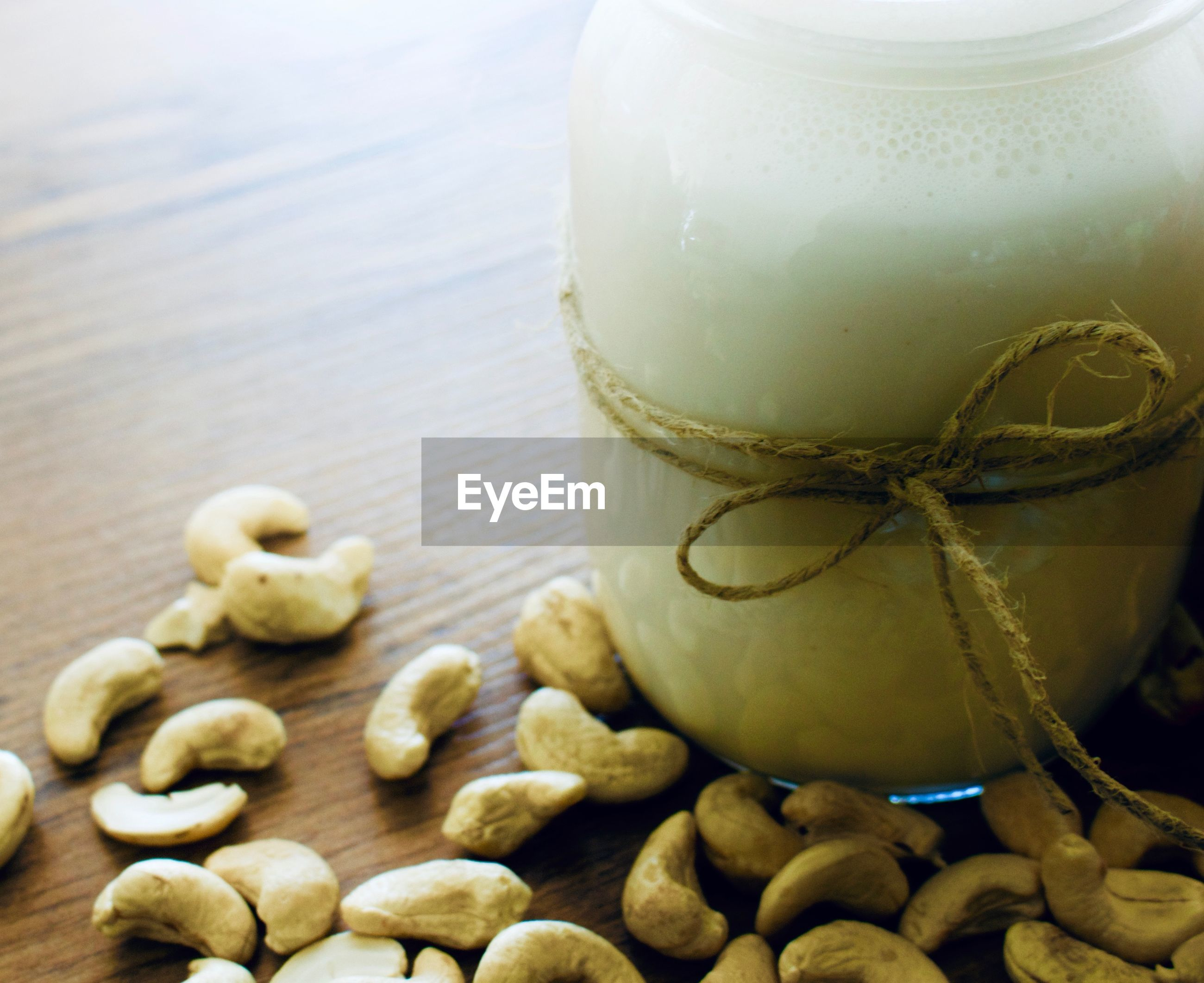 Close-up of drink in glass jar with cashews on table