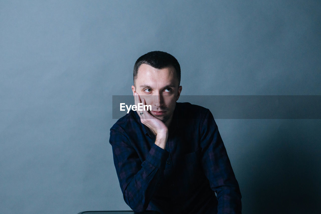 Thoughtful Man Sitting Against Wall