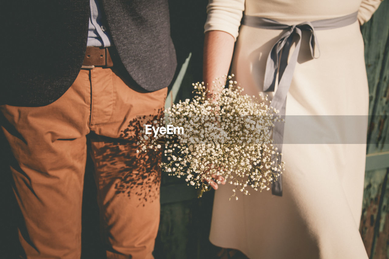 Midsection Of Bride And Bridegroom With Bouquet During Wedding Ceremony