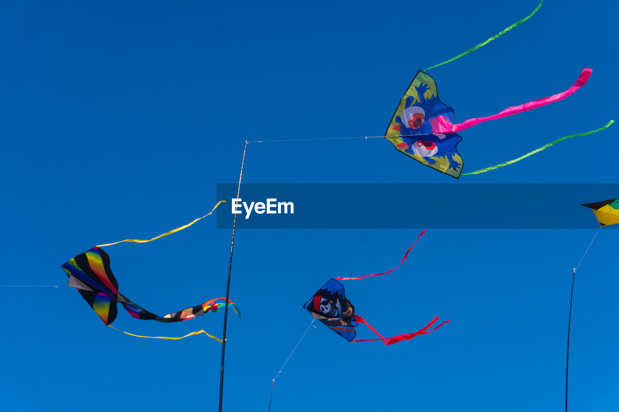 Low angle view of kites flying against blue sky