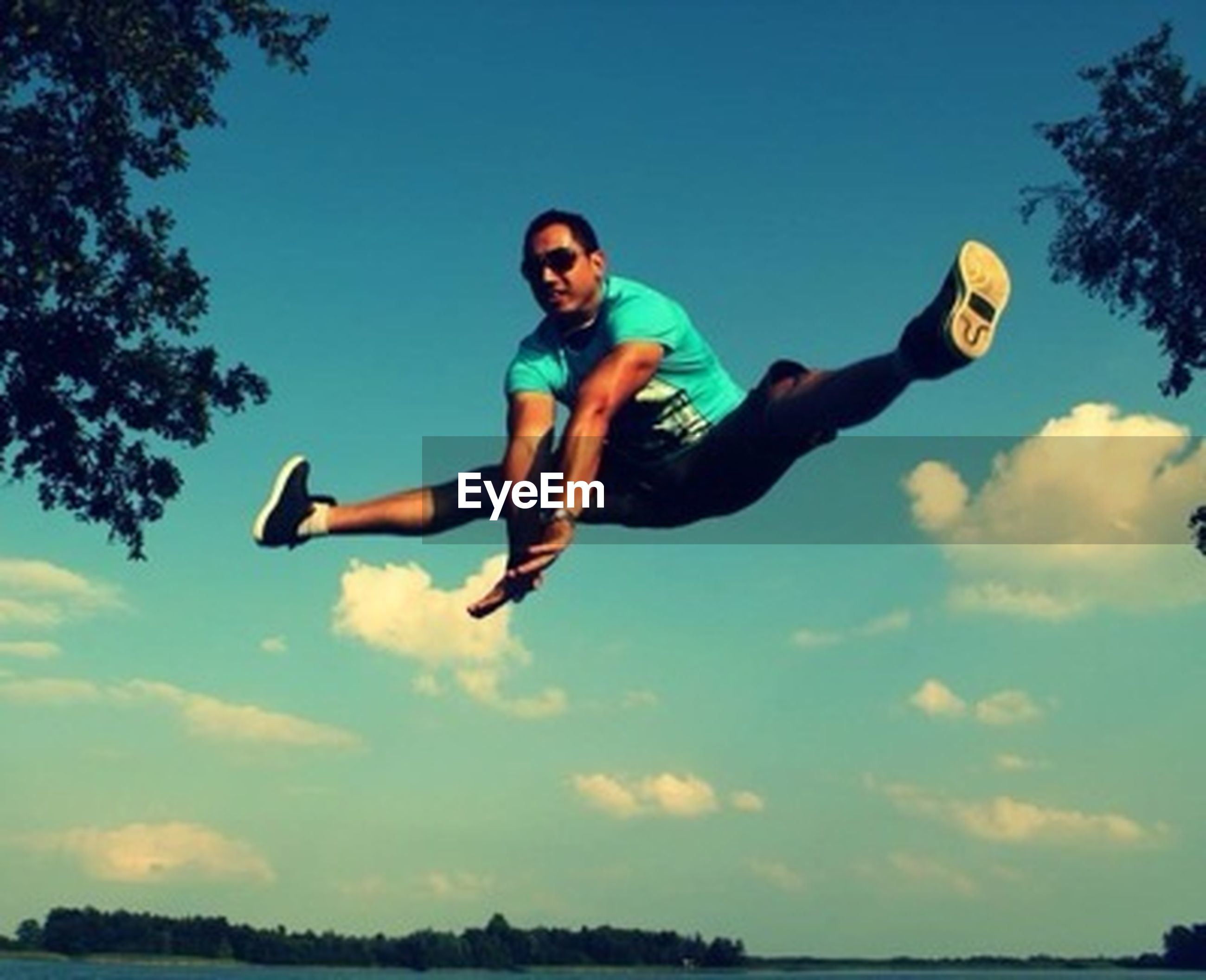 lifestyles, leisure activity, full length, person, fun, enjoyment, mid-air, casual clothing, young adult, happiness, childhood, young men, sky, jumping, boys, vacations, togetherness, smiling