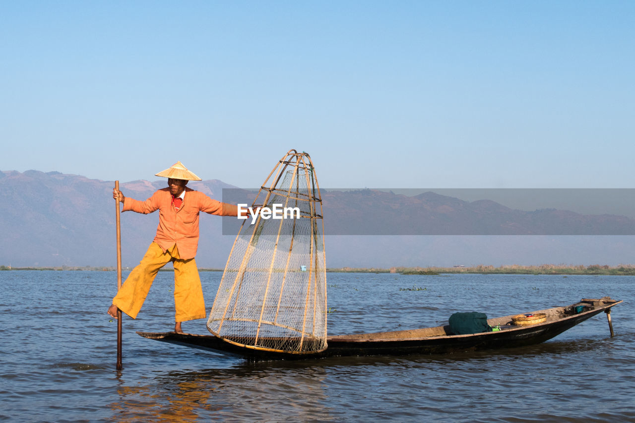 real people, hat, men, clear sky, outdoors, occupation, one person, nature, full length, water, asian style conical hat, mountain, fishing net, day, fisherman, women, nautical vessel, standing, working, sky, people
