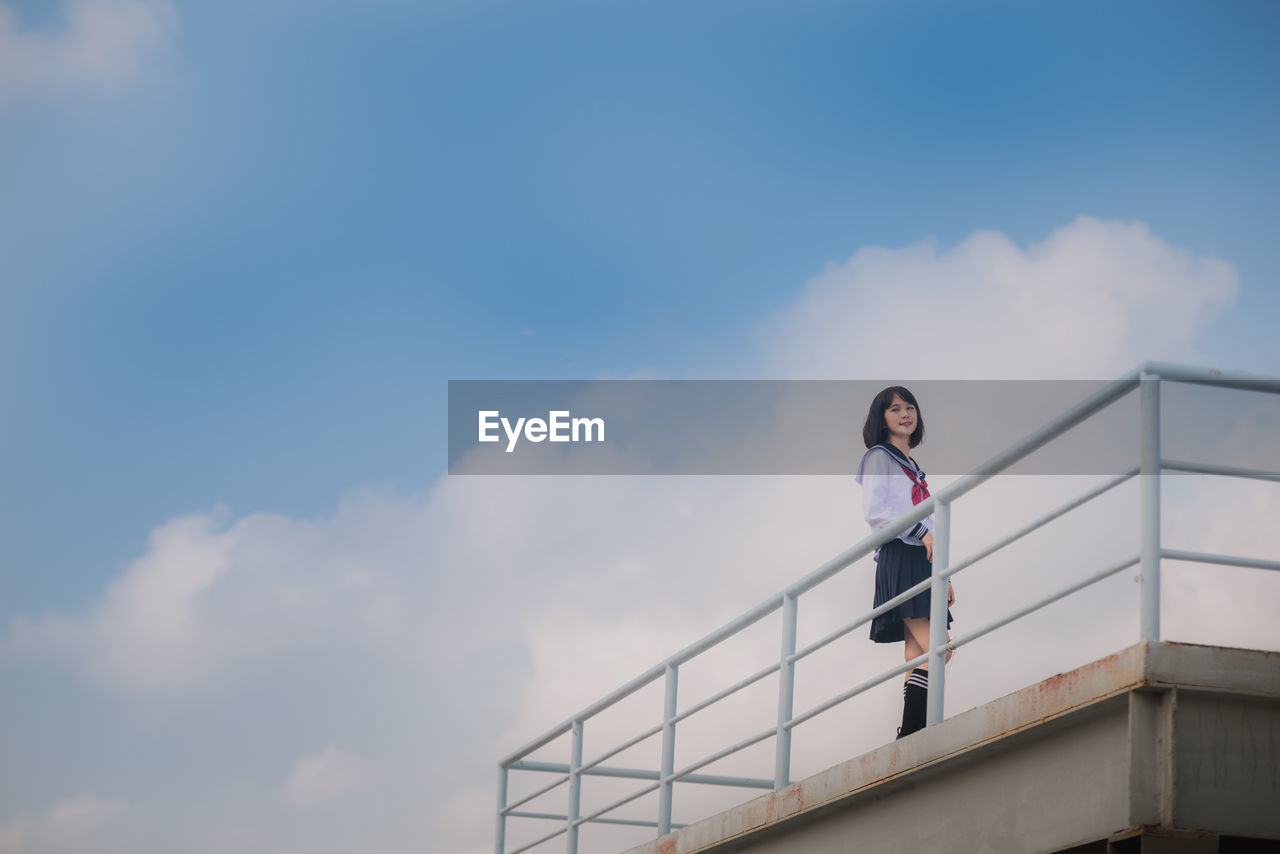 Low angle view of young woman wearing uniform while standing on balcony against sky