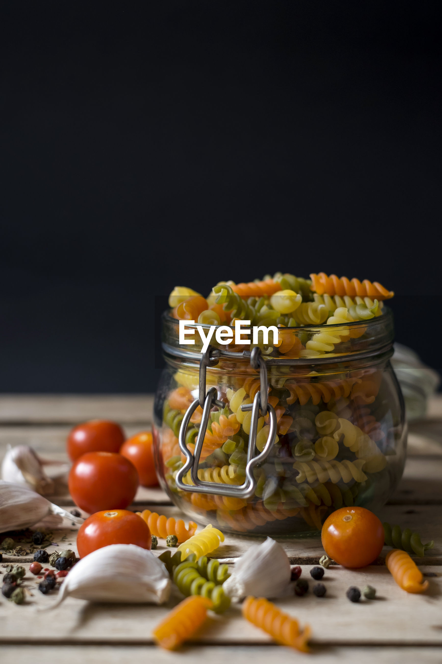 Close-up of pasta in jar with tomatoes on table against black background